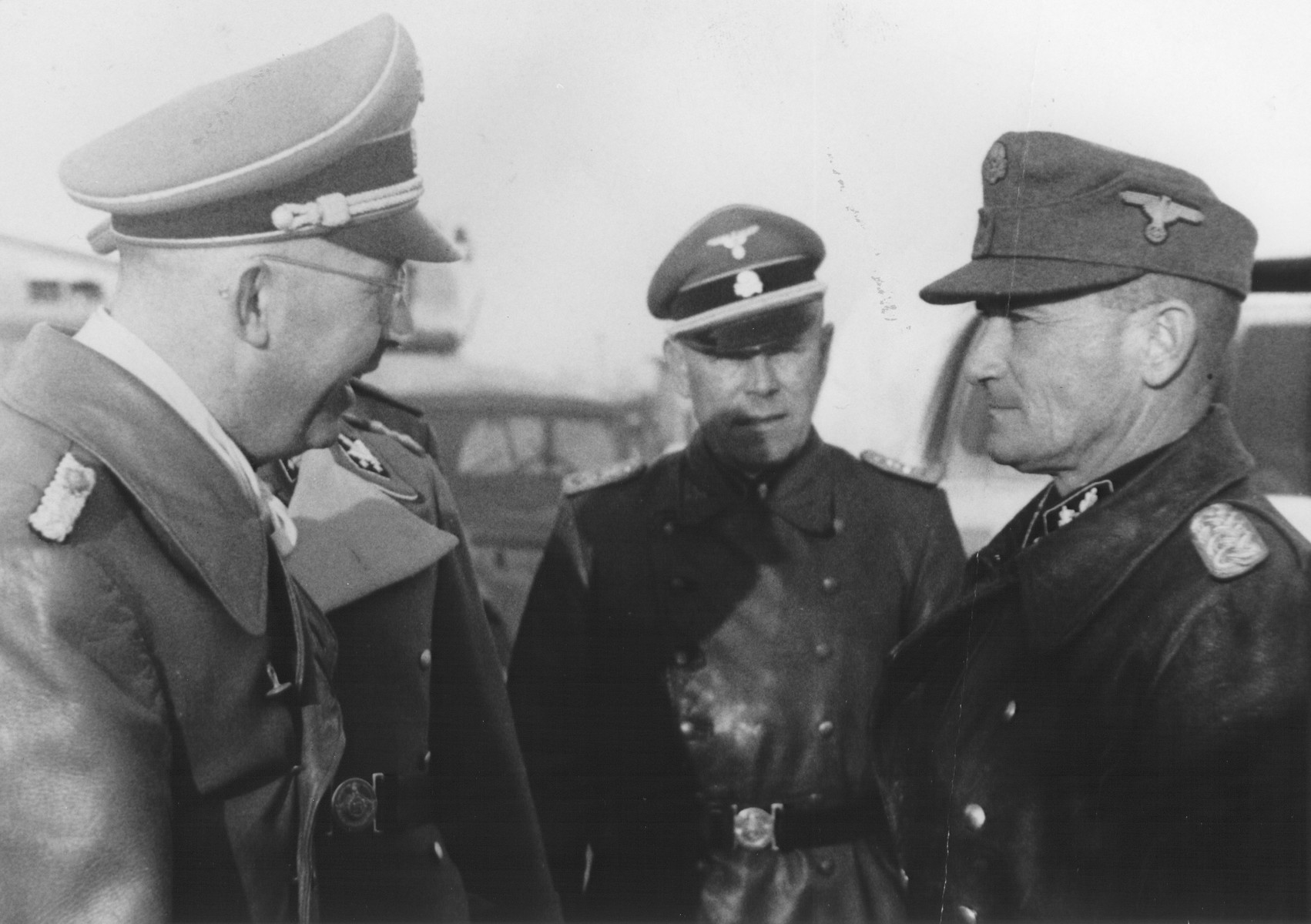Reichsfuehrer-SS Heinrich Himmler converses with a group of officers.  Pictured on the far right is SS-Gruppenfuhrer Generalleutnant der Waffen-SS Fritz von Scholz.  At the center is Himmler's bodyguard, SS-Hauptsturmfuhrer Josef Kiermaier.