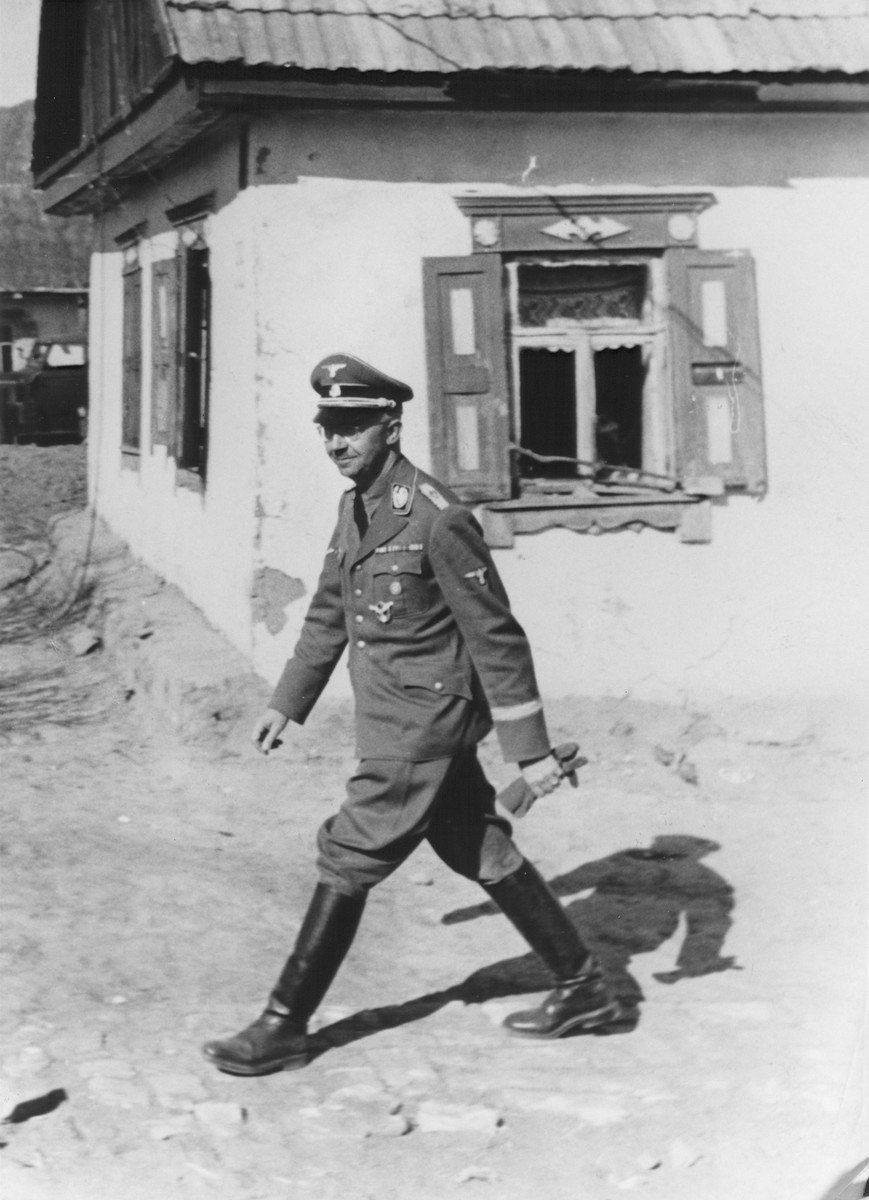 Reichsfuehrer-SS Heinrich Himmler walks past a cottage [probably during a visit to the Waffen-SS Armored Division Wiking].
