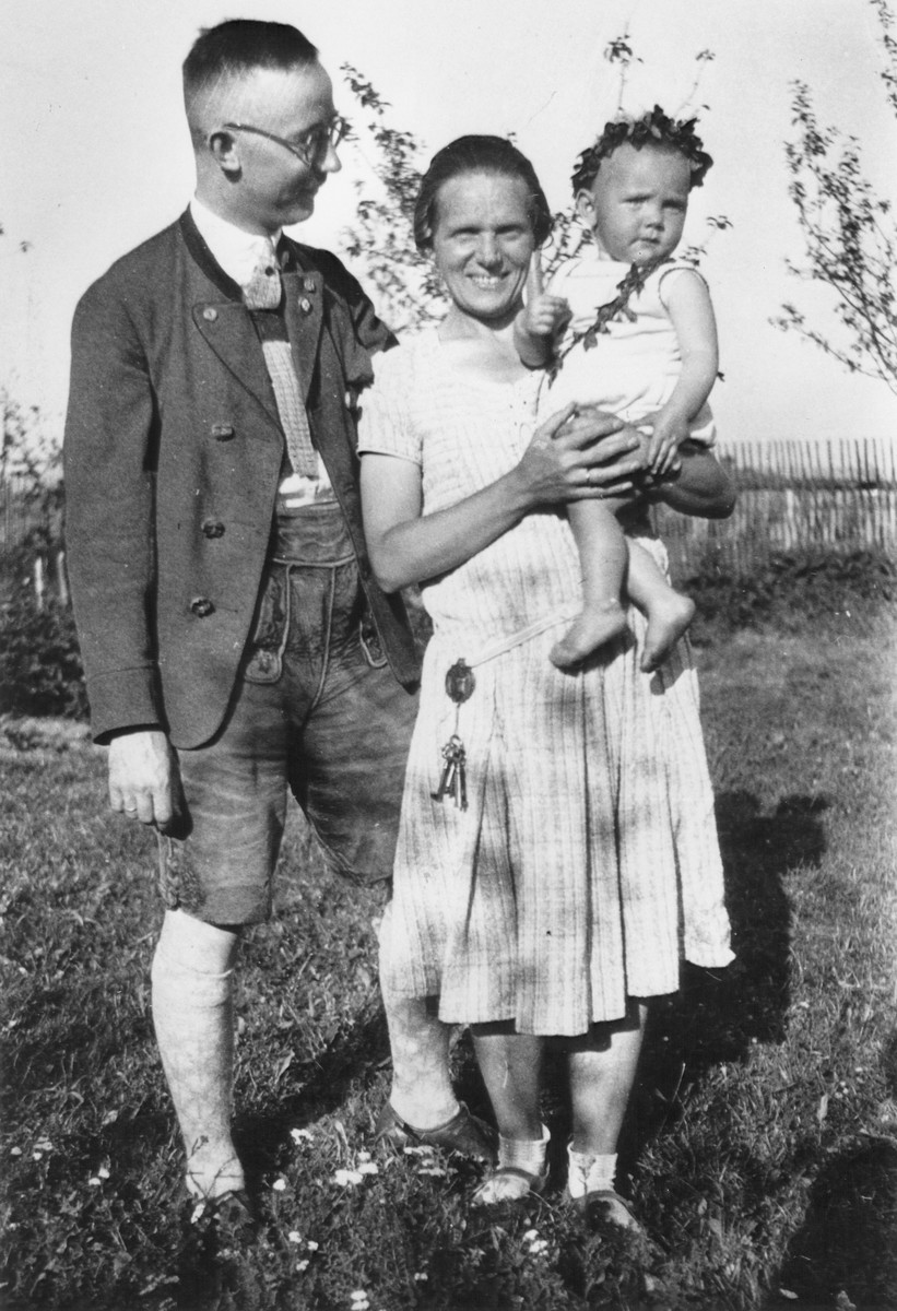 Heinrich and Margarete Himmler pose outside in a yard with their infant daughter Gudrun.