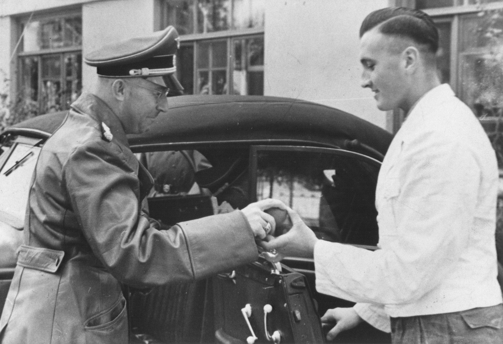Reichsfuehrer-SS Heinrich Himmler accepts a birthday gift from a server at Hochwald before getting into an automobile.