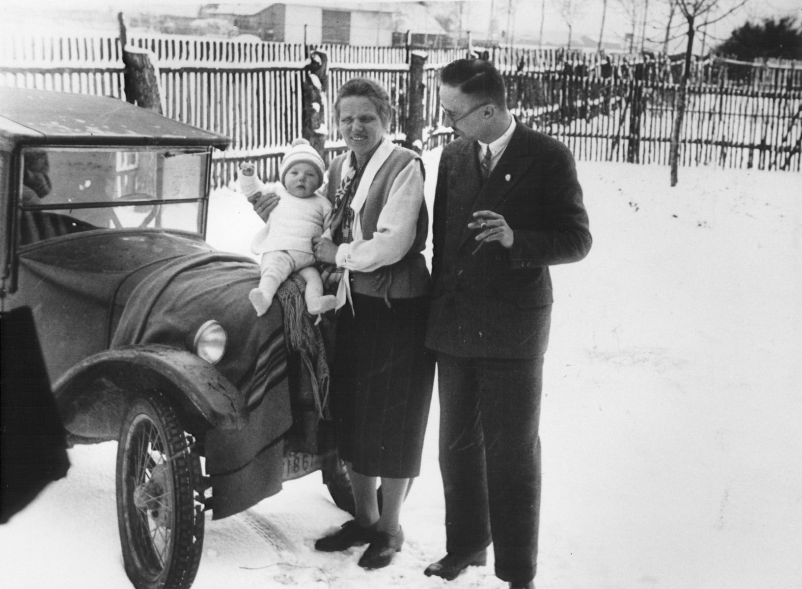 Heinrich and Margarete Himmler pose with their infant daughter Gudrun outside in the snow in front of their car.