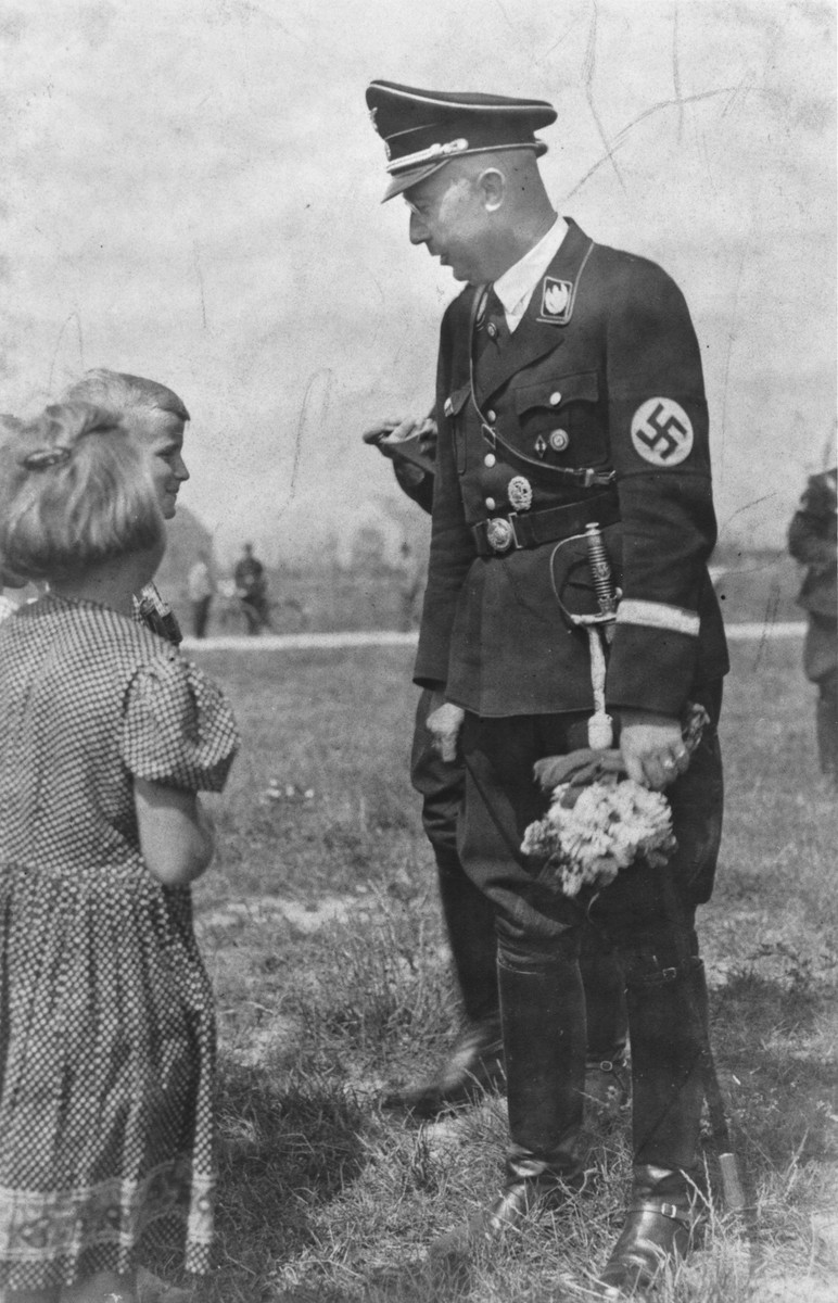 Reichsfuehrer-SS Heinrich Himmler converses with two children who have just presented him with a bouquet of flowers.