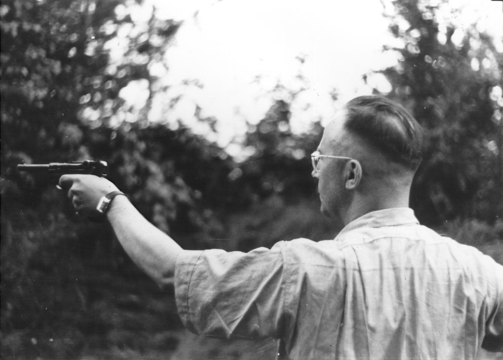 Heinrich Himmler shooting a pistol.