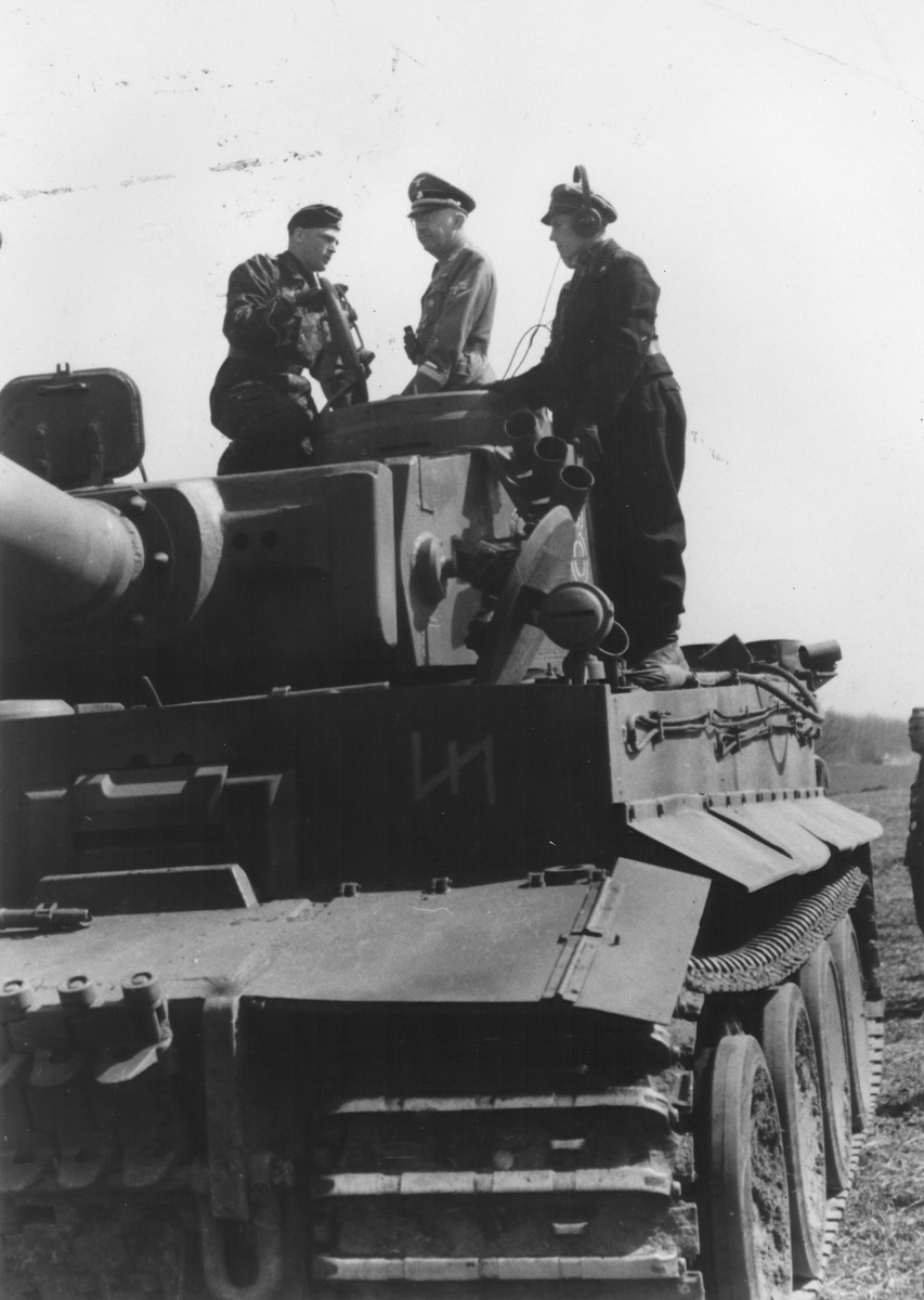 Reichsfuehrer-SS Heinrich Himmler stands on top of a tank with two German soldiers.