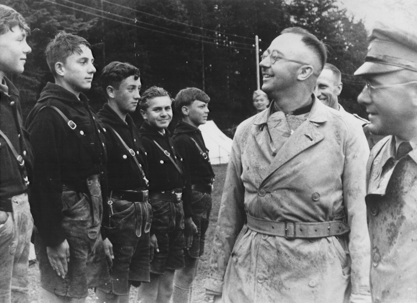 During a visit to the Hochland youth camp, Reichsfuehrer-SS Heinrich Himmler (center) and camp leader Emil Klein (right, in profile) review a group of German youth who are standing in formation.