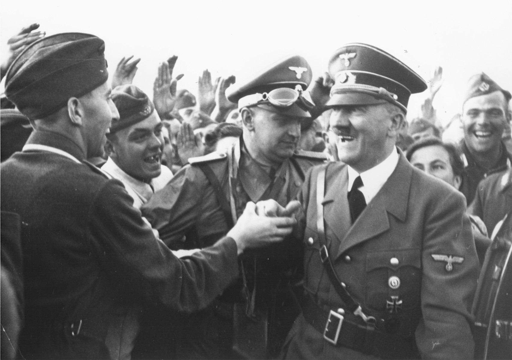 A smiling Adolf Hitler greets a soldier.  Pictured at the center with goggles is Hitler's aide-de-camp Heinz Linge.