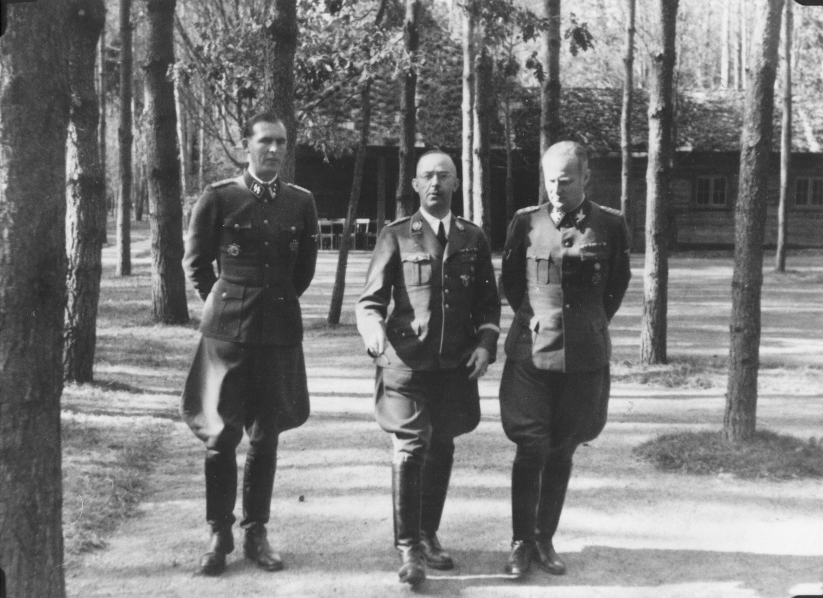 Reichsfuehrer-SS Heinrich Himmler strolls with two other SS officials [probably at Wolfsschanze (Wolf's Lair), Hitler's field headquarters in Rastenburg, East Prussia].   Pictured from left to right are: Richard Schulze-Kossens, Himmler and Karl Wolff.