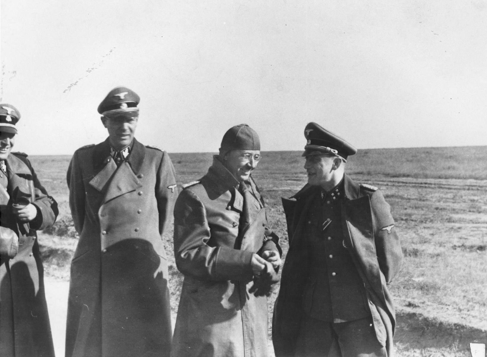 Reichsfuehrer-SS Heinrich Himmler (center) confers with SS and Police Leader Hans Adolf Pruetzmann (extreme left) and Ludolf Herman von Alvensleben (second from the left) during a visit to the Crimea.  During this visit, Himmler gave Pruetzmann a written order to kill all the residents of the Pinsk ghetto (population 16,200), then, the largest remaining Jewish community in the Ukraine.  The community was killed between October 29 and November 1, 1942.