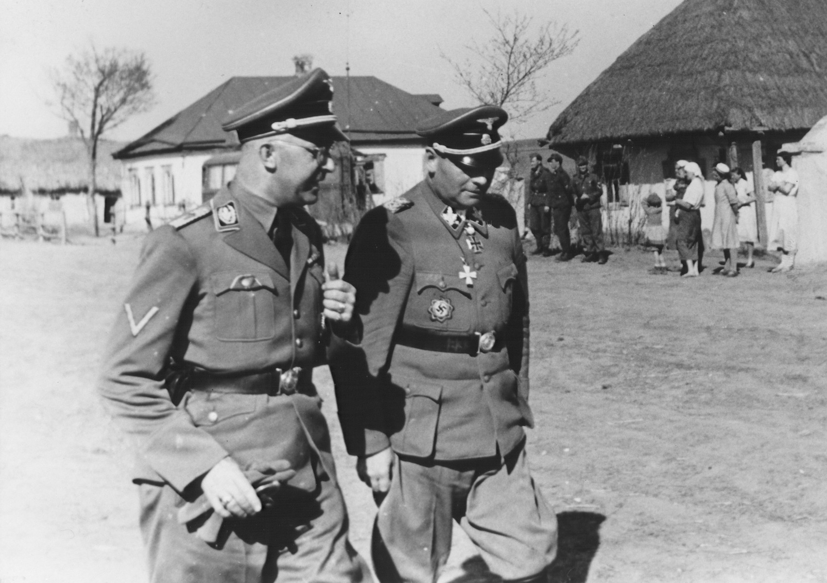 Reichsfuehrer-SS Heinrich Himmler (left) strolls through a village in the company of Waffen-SS Armored Division Wiking chief, SS-Brigadefuehrer and Major General Felix Steiner.  Steiner was commander of the Wiking Division from December 1940 through May 1943. Himmler may have visited the Wiking Division during his visits to Waffen-SS and Einsatzgruppe D units in Kriwoj Rog and Nikoljew on October 3-5, 1941.  During this tour, Himmler ordered that gas vans be deployed to Nowgorod to kill the mentally ill.  In conjunction with Himmler's visit, a teilkommando of Einsatzgruppe D shot Jewish women for the first time. [Himmler Dienstkalender, pp.224-25]