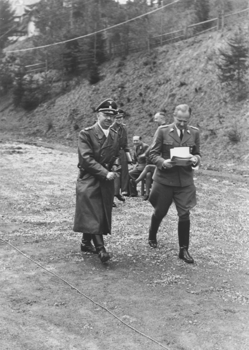 Taken on his birthday, Reichsfuehrer-SS Heinrich Himmler converses with Karl Wolff (right) as they walk along an unpaved road. Himmler's former adjunct Jochen Pieper can be seen over Himmler's left shoulder.