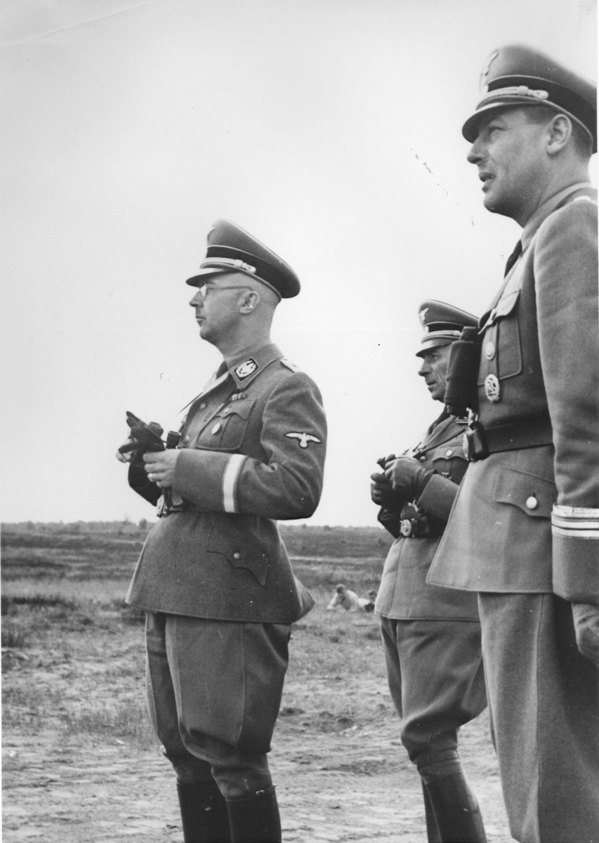 Reichsfuehrer-SS Heinrich Himmler stands outside in a field holding a pair of binoculars in the company of Paul Hausser (second from the right) and possibly Wilhelm Stuckart.
