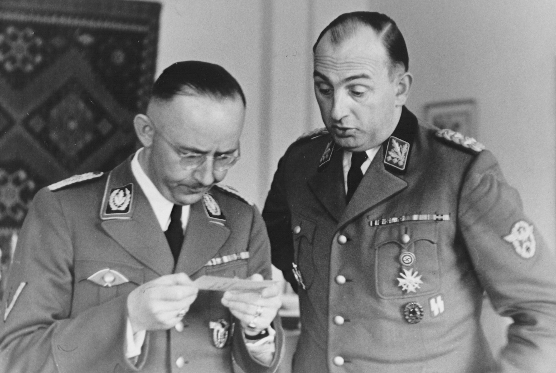 Reichsfuehrer-SS Heinrich Himmler looks at a photograph on his birthday with Chief of the Order Police, Kurt Daluege at SS headquarters in Hegewald bei Zhitomir, Ukraine.
