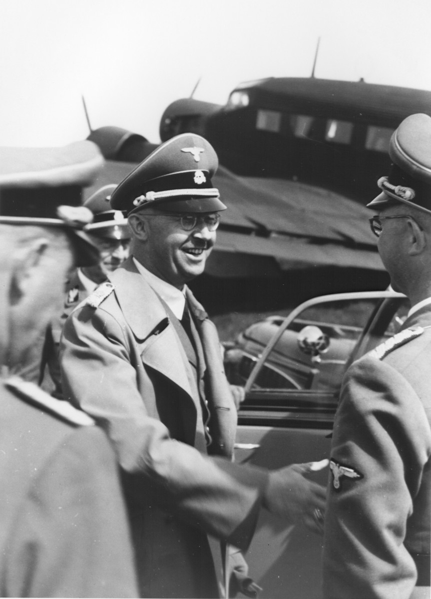 Reichsfuehrer-SS Heinrich Himmler shaking hands with Hermann Bartels at the airport in Paderborn, Germany.  Also pictured behind Himmler is SS-Gruppenfuehrer Siegfried Taubert.