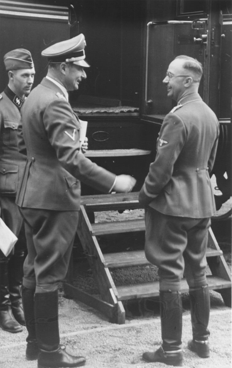 Reichsfuehrer-SS Heinrich Himmler speaks to Karl Wolff (center) in front of a train.