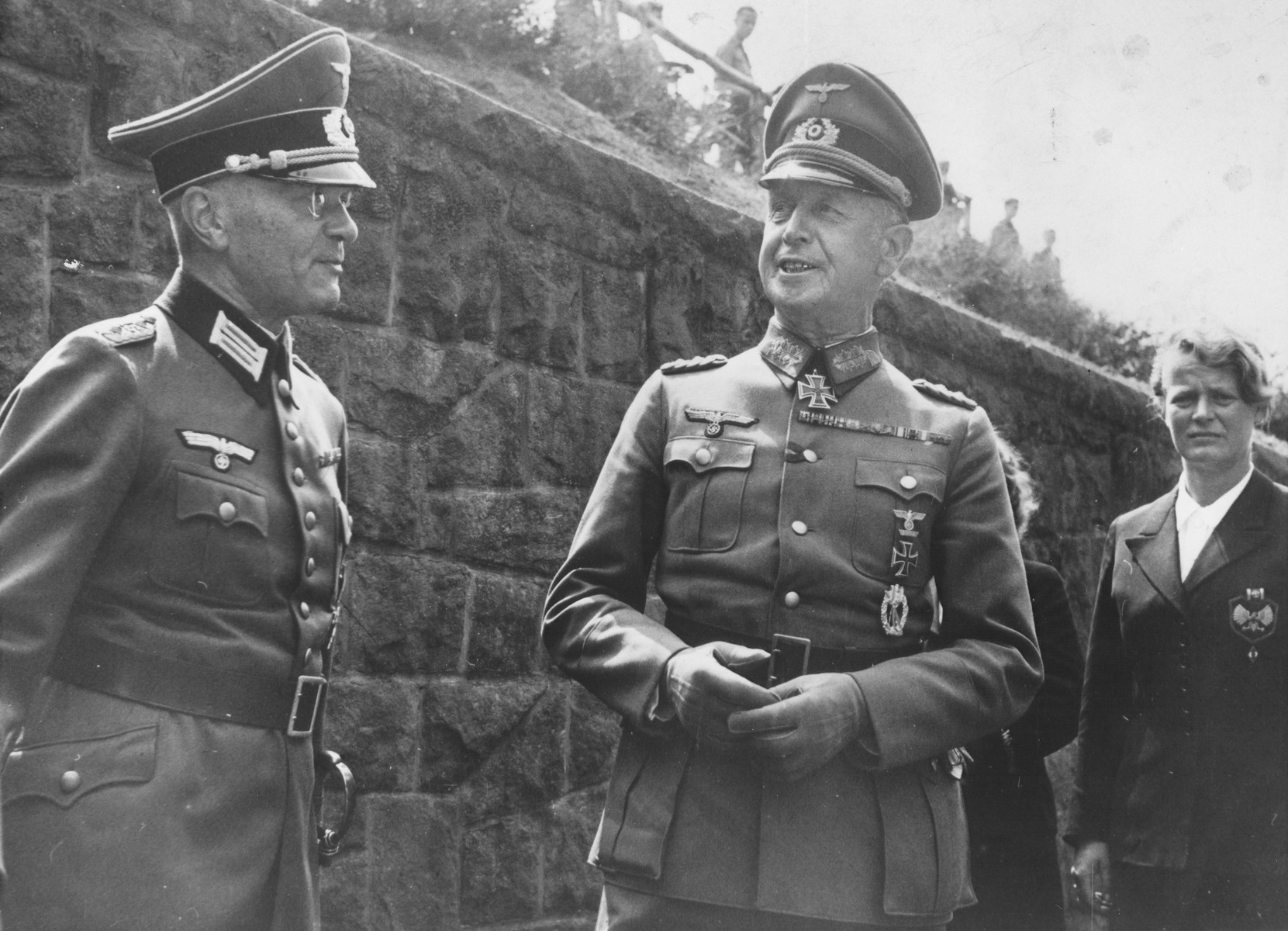 Two high-ranking German military officers converse in front of a stone wall.