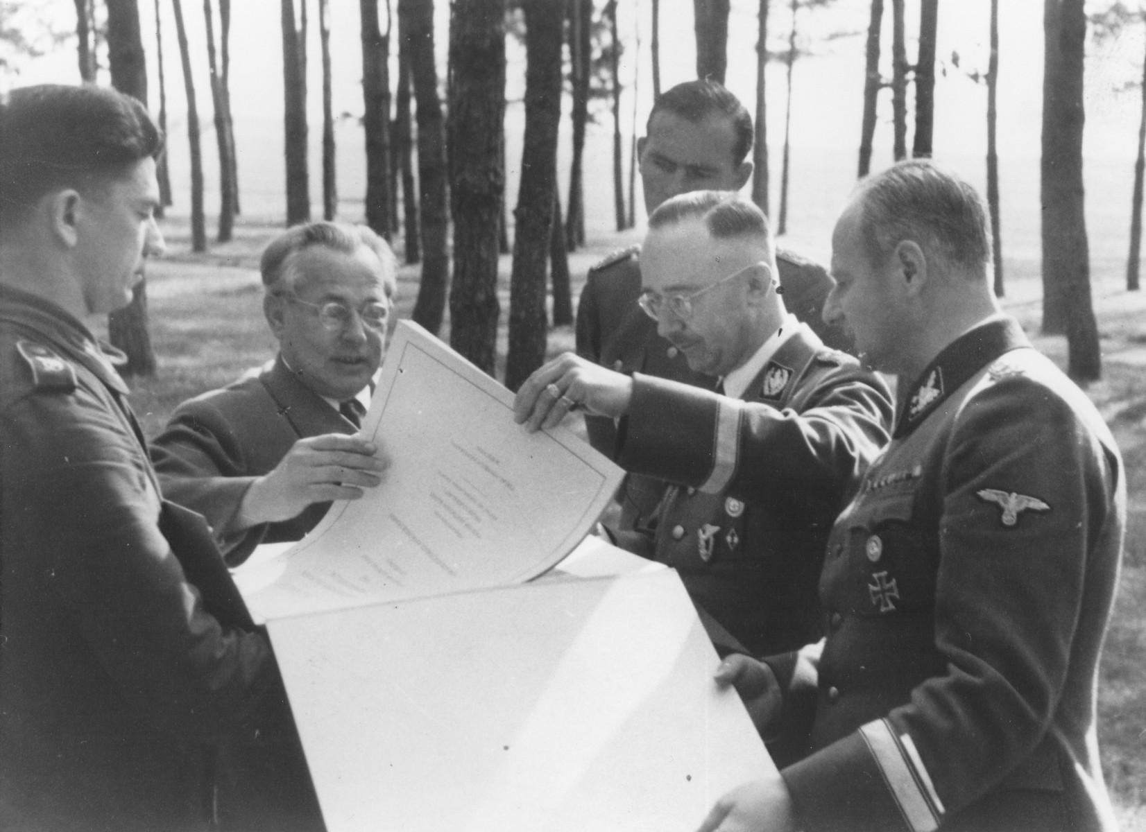 "Reichsfuehrer-SS Heinrich Himmler views a presentation album entitled, ""Grosse Deutsche Kunstausstellung 1941"" [probably at Wolfsschanze (Wolf's Lair), Hitler's field headquarters in Rastenburg, East Prussia].   Pictured clockwise from the left are: unknown, Heinrich Hoffmann, Richard Schulze-Kossens, Himmler, and Karl Wolff."