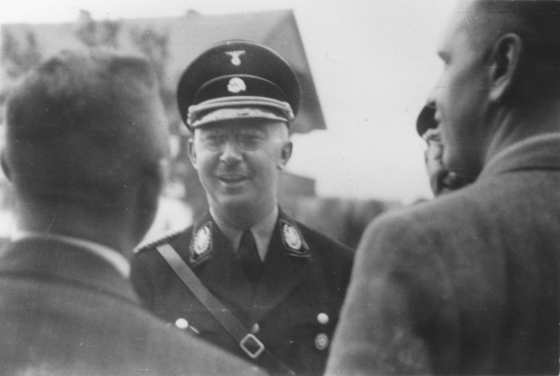 Reichsfuehrer-SS Heinrich Himmler converses with two civilians.