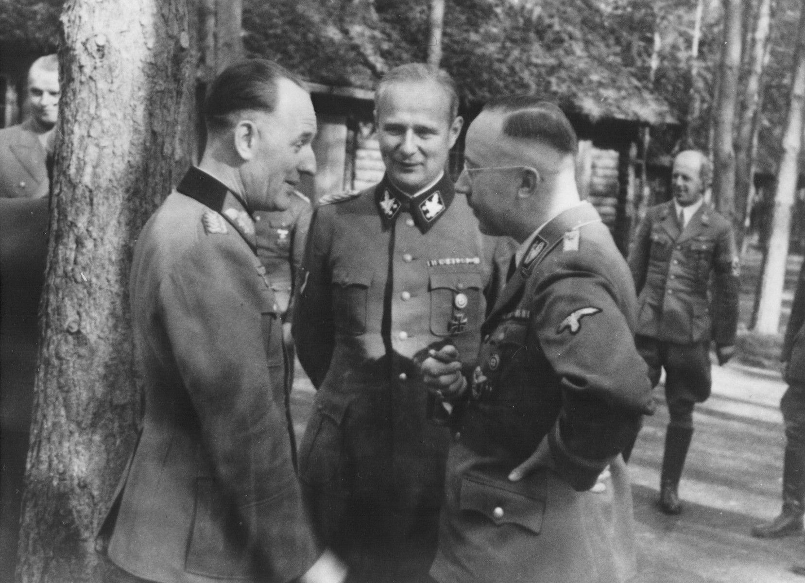 Reichsfuehrer-SS Heinrich Himmler converses with two German officers.  Pictured in the foreground from left to right are: General Rudolf Schmundt, Karl Wolff and Heinrich Himmler.  In the back on the far right is SS-Gruppenfuehrer Helmut Friedrichs.