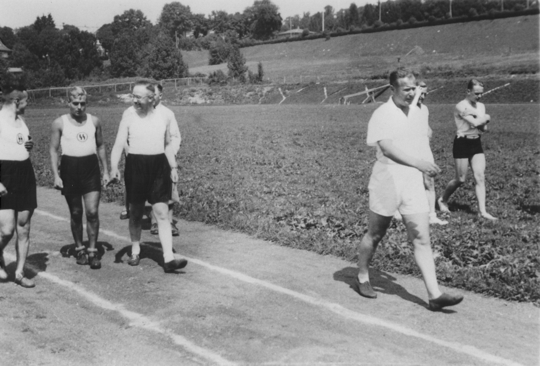 Heinrich Himmler walks along an outdoor track at the SS officers school in Bad Tolz, Germany.  Also pictured is Himmler's adjutant Karl Wolff (ahead of Himmler in the white shirt and shorts).