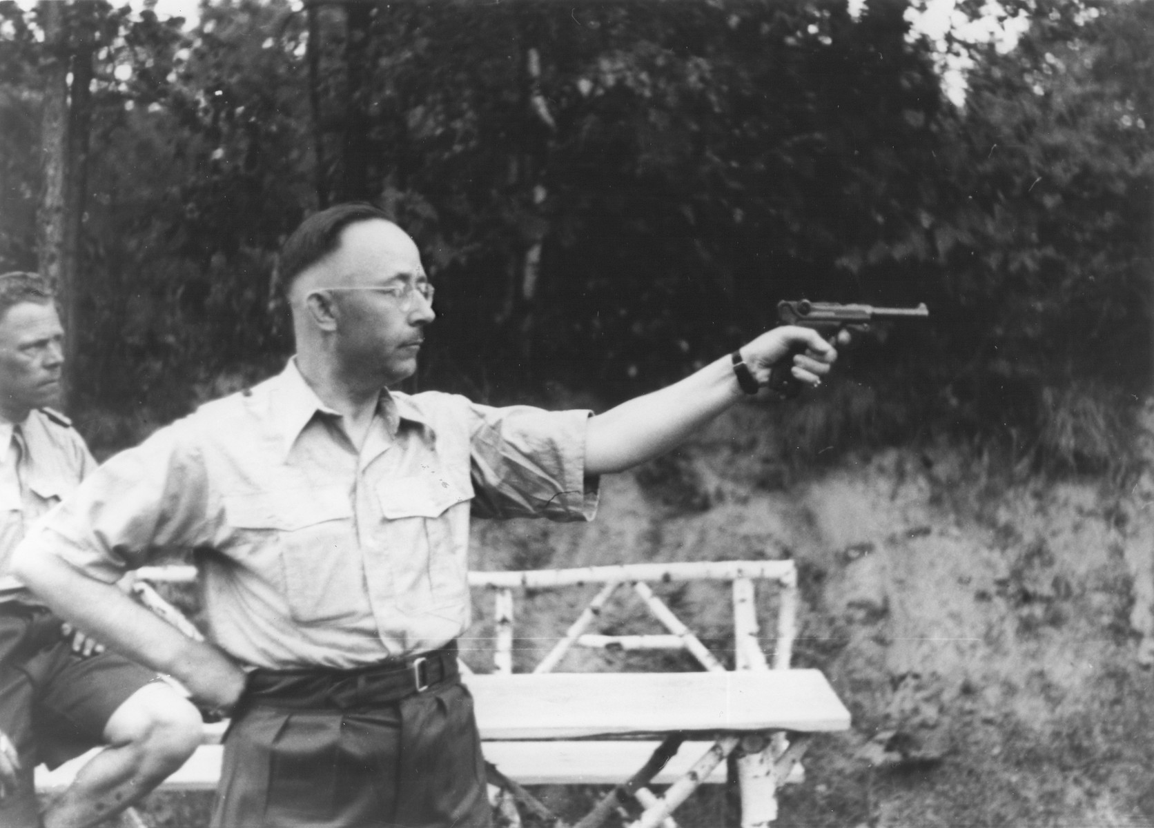 Heinrich Himmler shoots a pistol while Kiermaier watches in the background.