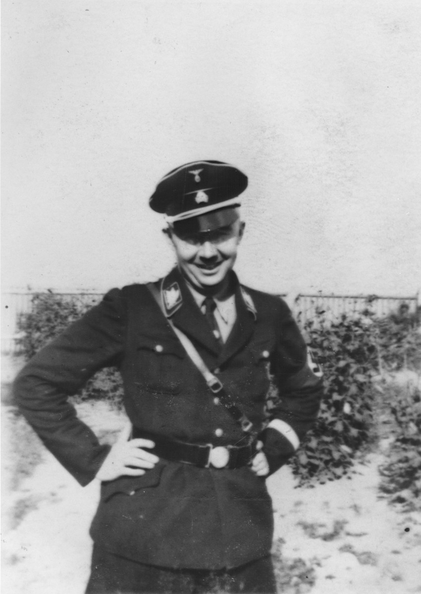 Reichsfuehrer-SS Heinrich Himmler poses outside in uniform with his hands on his hips.