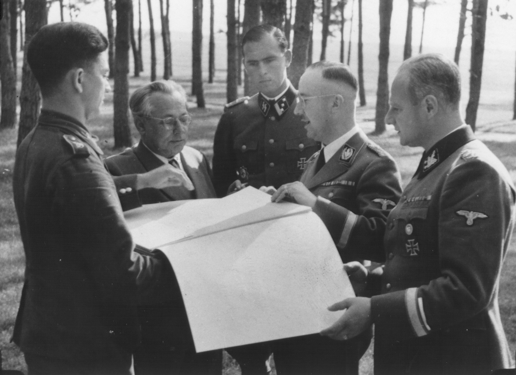 "Reichsfuehrer-SS Heinrich Himmler views a presentation album entitled, ""Grosse Deutsche Kunstausstellung 1941"" [probably at Wolfsschanze (Wolf's Lair), Hitler's field headquarters in Rastenburg, East Prussia].   Pictured from left to right are: unknown, Heinrich Hoffmann, Richard Schulze-Kossens, Himmler, and Karl Wolff."
