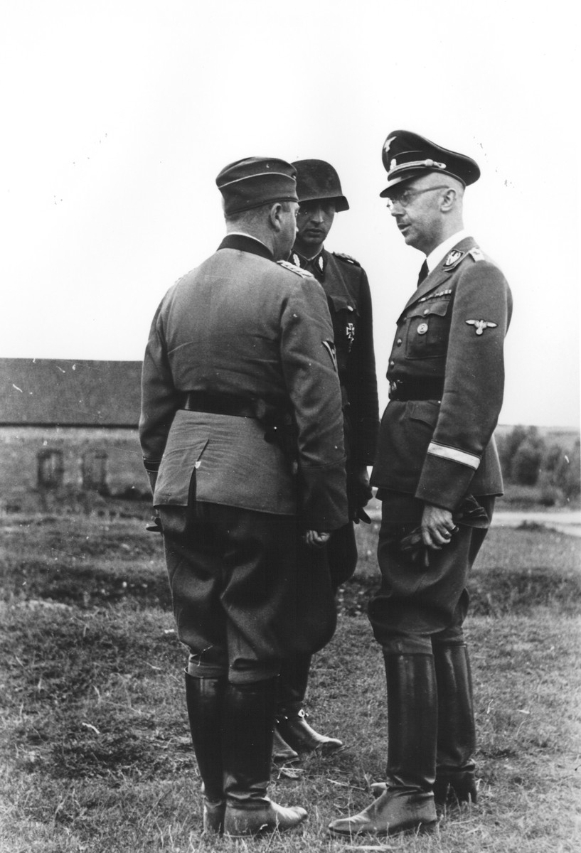 Heinrich Himmler consults with commanders of a Waffen SS calvary brigade in the eastern territories.  Pictured are SS-Brigadefuehrer Kurt Knoblauch (with back to camera) and SS-Standartenfuehrer Hermann Fegelein (center) and Reichsfuehrer-SS Heinrich Himmler (right).