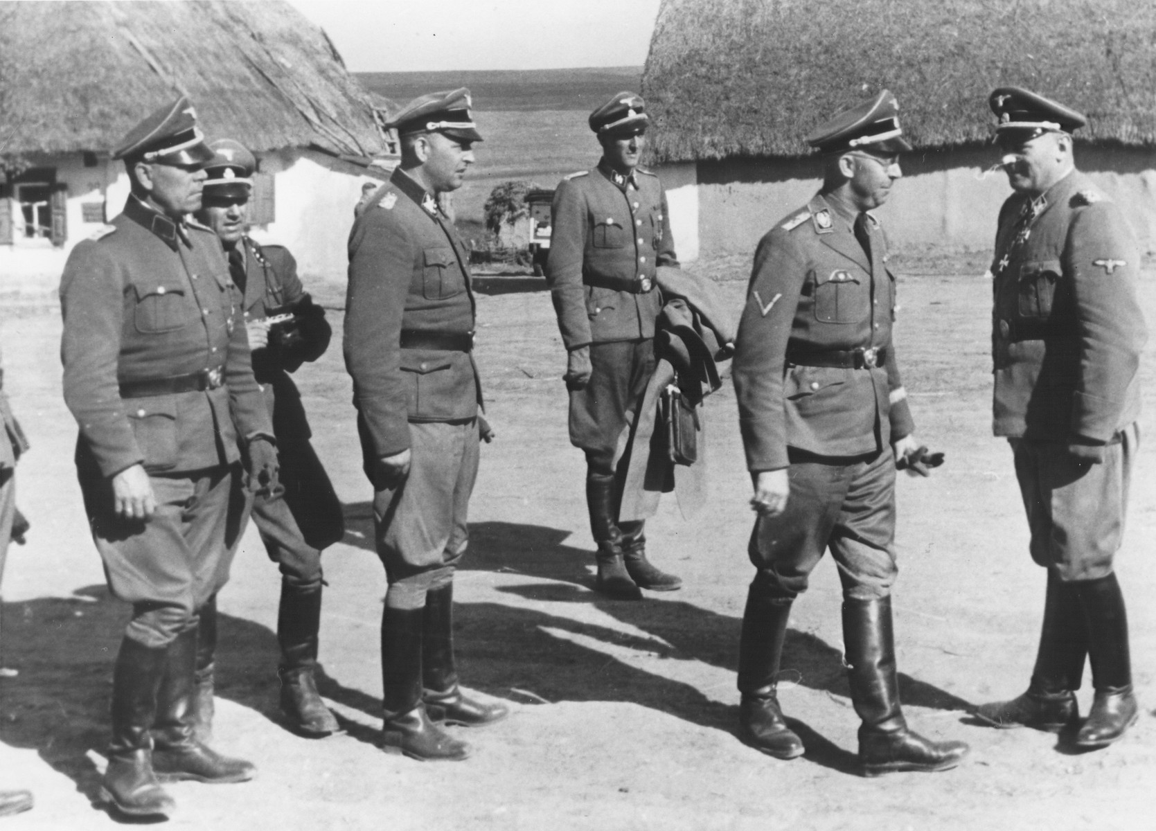 Reichsfuehrer-SS Heinrich Himmler (second from right) confers with Waffen-SS Armored Division Wiking chief, SS-Brigadefuehrer and Major General Felix Steiner (right) during a visit to a village.  Steiner was commander of the Wiking Division from December 1940 through May 1943. Himmler may have visited the Wiking Division during his visits to Waffen-SS and Einsatzgruppe D units in Kriwoj Rog and Nikoljew on October 3-5, 1941.  During this tour, Himmler ordered that gas vans be deployed to Nowgorod to kill the mentally ill.  In conjunction with Himmler's visit, a teilkommando of Einsatzgruppe D shot Jewish women for the first time. [Himmler Dienstkalender, pp.224-25]  Original caption reads: Truppenbetreuung SS Division Wiking.