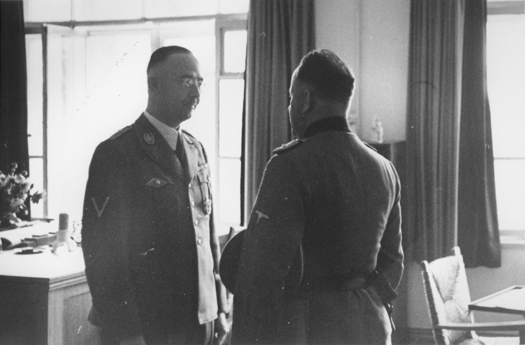 SS-Reichsfuehrer Heinrich Himmler confers with an unknown person in his office at SS headquarters in the Hegewald bei Zhitomir compound.