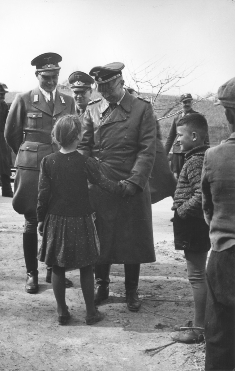 Reichsfuehrer-SS Heinrich Himmler speaks to a young girl.