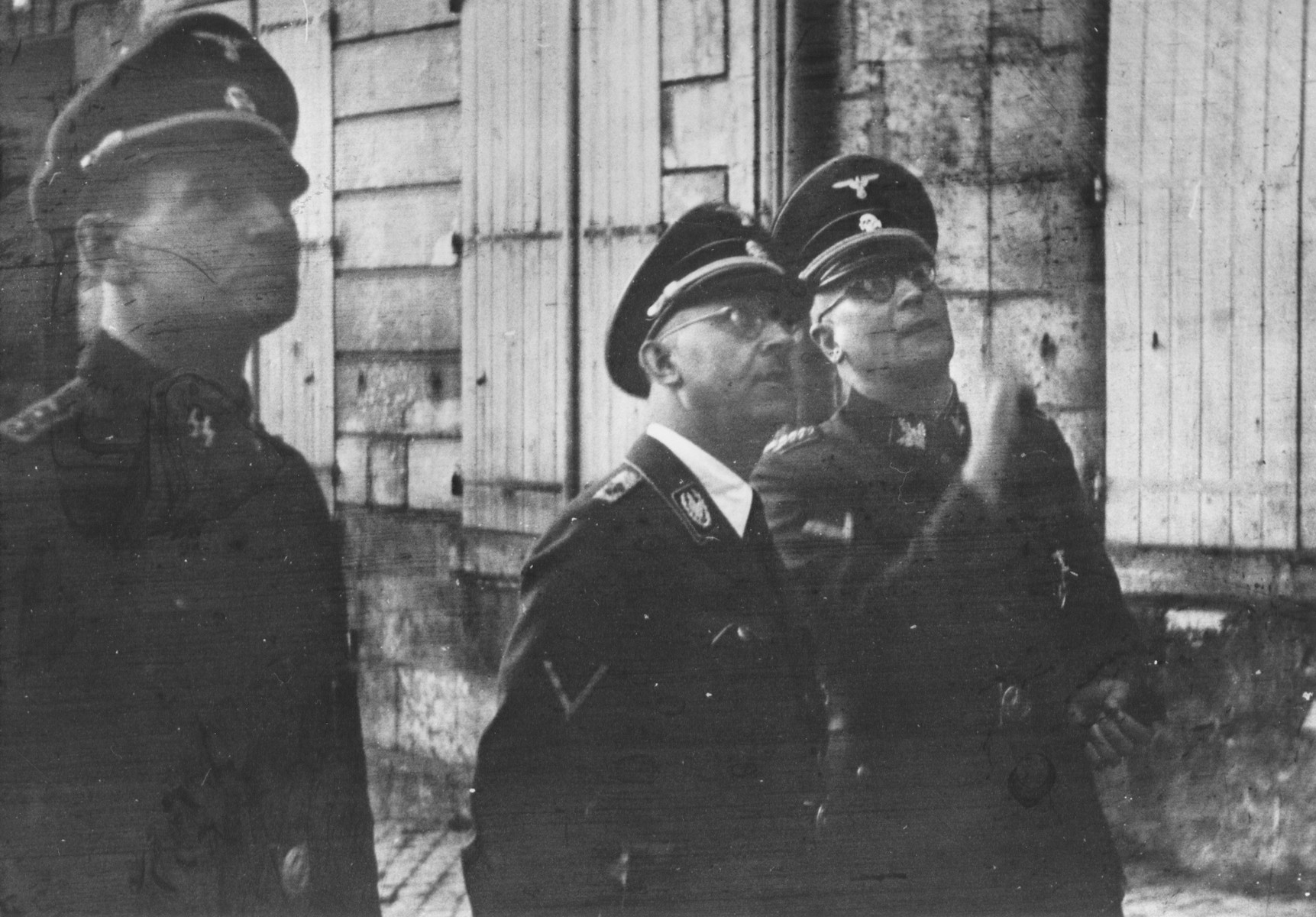 Reichsfuehrer-SS Heinrich Himmler (center) stands outside with Lothar Debes (rights) and another unidentified SS officer.