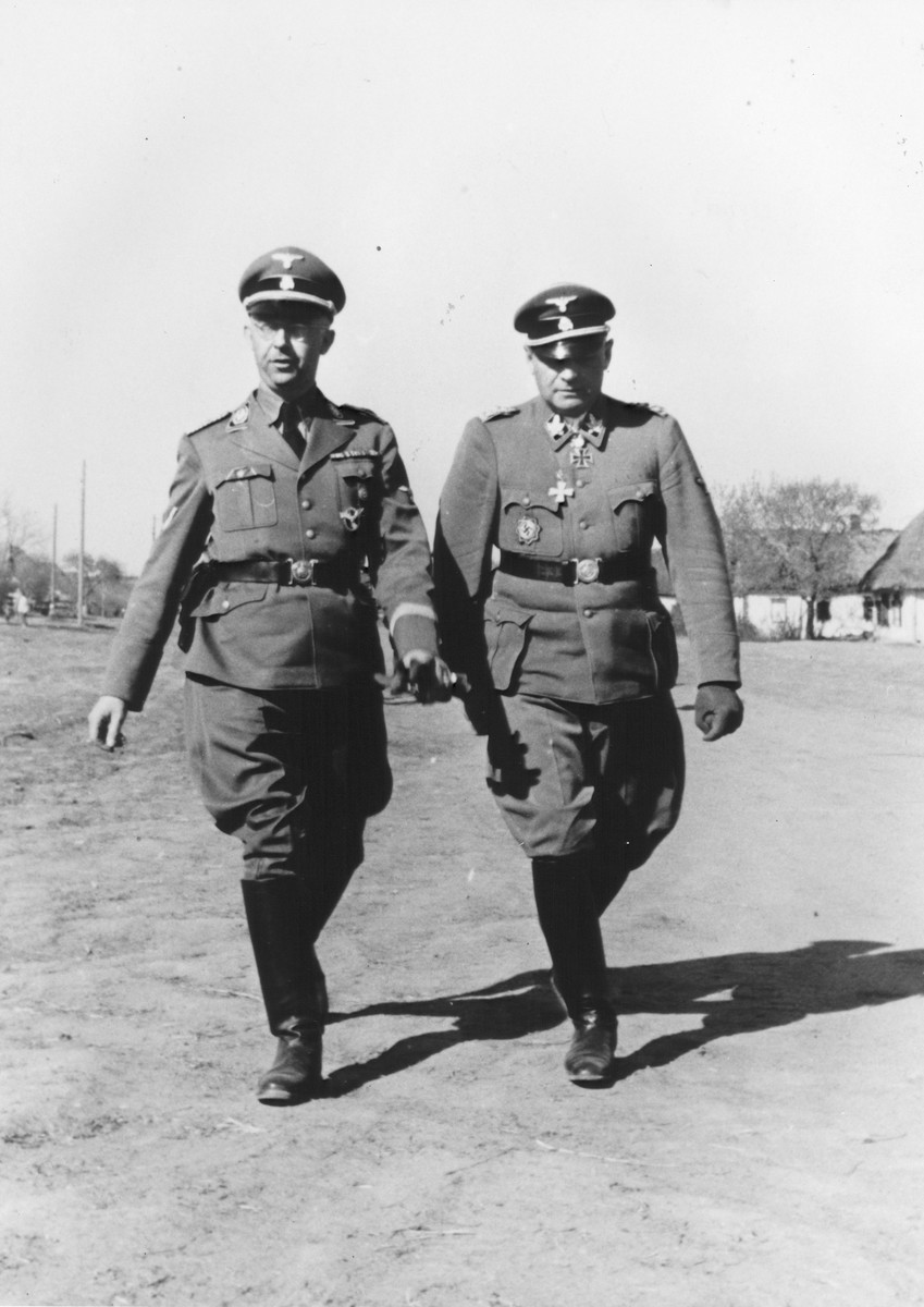 Reichsfuehrer-SS Heinrich Himmler (left) strolls through a village in the company of Waffen-SS Armored Division Wiking chief, SS-Brigadefuehrer and Major General Felix Steiner.  Steiner was commander of the Wiking Division from December 1940 through May 1943. Himmler may have visited the Wiking Division during his visits to Waffen-SS and Einsatzgruppe D units in Kriwoj Rog and Nikoljew on October 3-5, 1941.  During this tour, Himmler ordered that gas vans be deployed to Nowgorod to kill the mentally ill.  In conjunction with Himmler's visit, a teilkommando of Einsatzgruppe D shot Jewish women for the first time. [Himmler Dienstkalender, pp.224-25]  Original caption reads: Truppenbetreuung SS Division Wiking, Abt. VI.