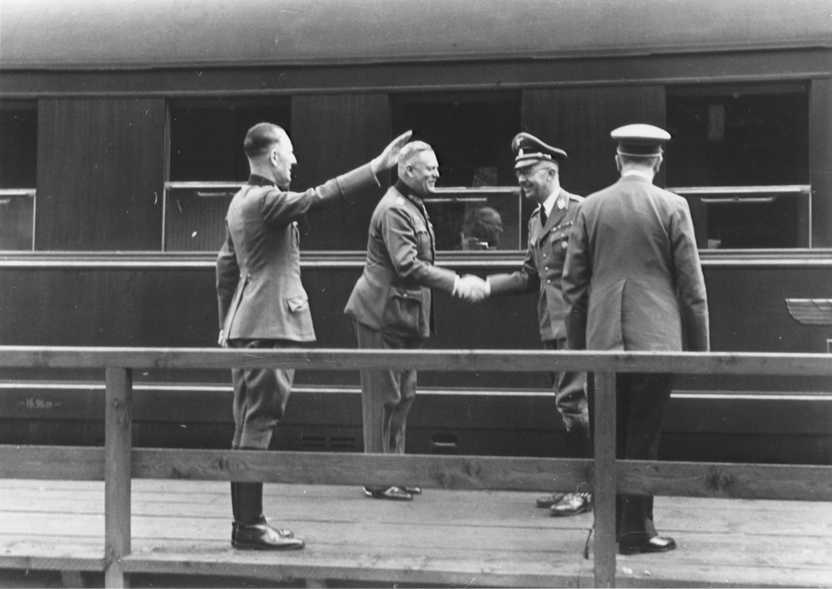 "Reichsfuehrer-SS Heinrich Himmler shakes hands with Wilhelm Keitel on a train platform.  Pictured from left to right are: Rudolf Schmundt (""chief adjutant of the Wehrmacht appointed to the Fuehrer""), Wilhelm Keitel, Heinrich Himmler and Adolf Hitler."