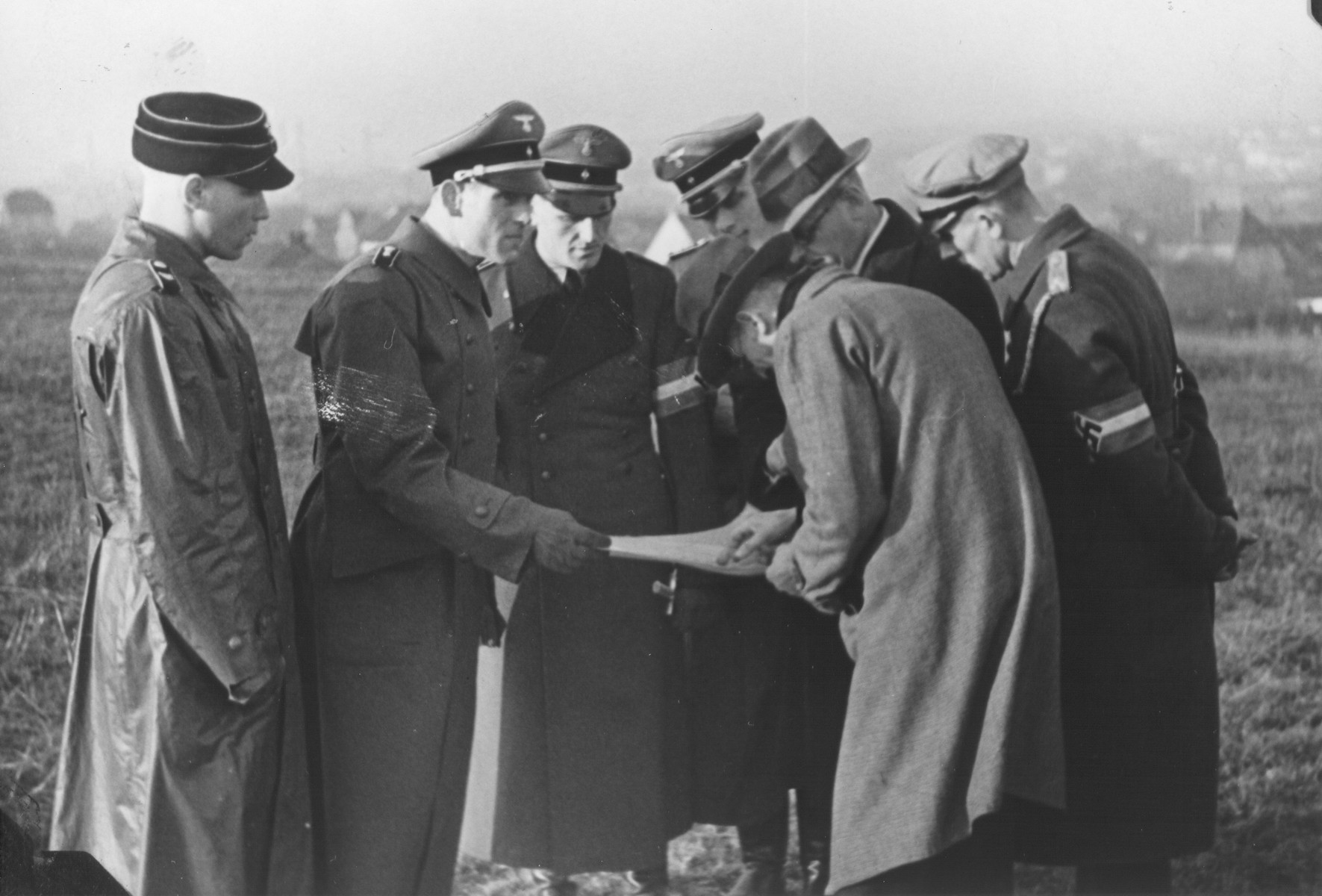 A group of uniformed Germans look on as two civilians study a map in an open field.