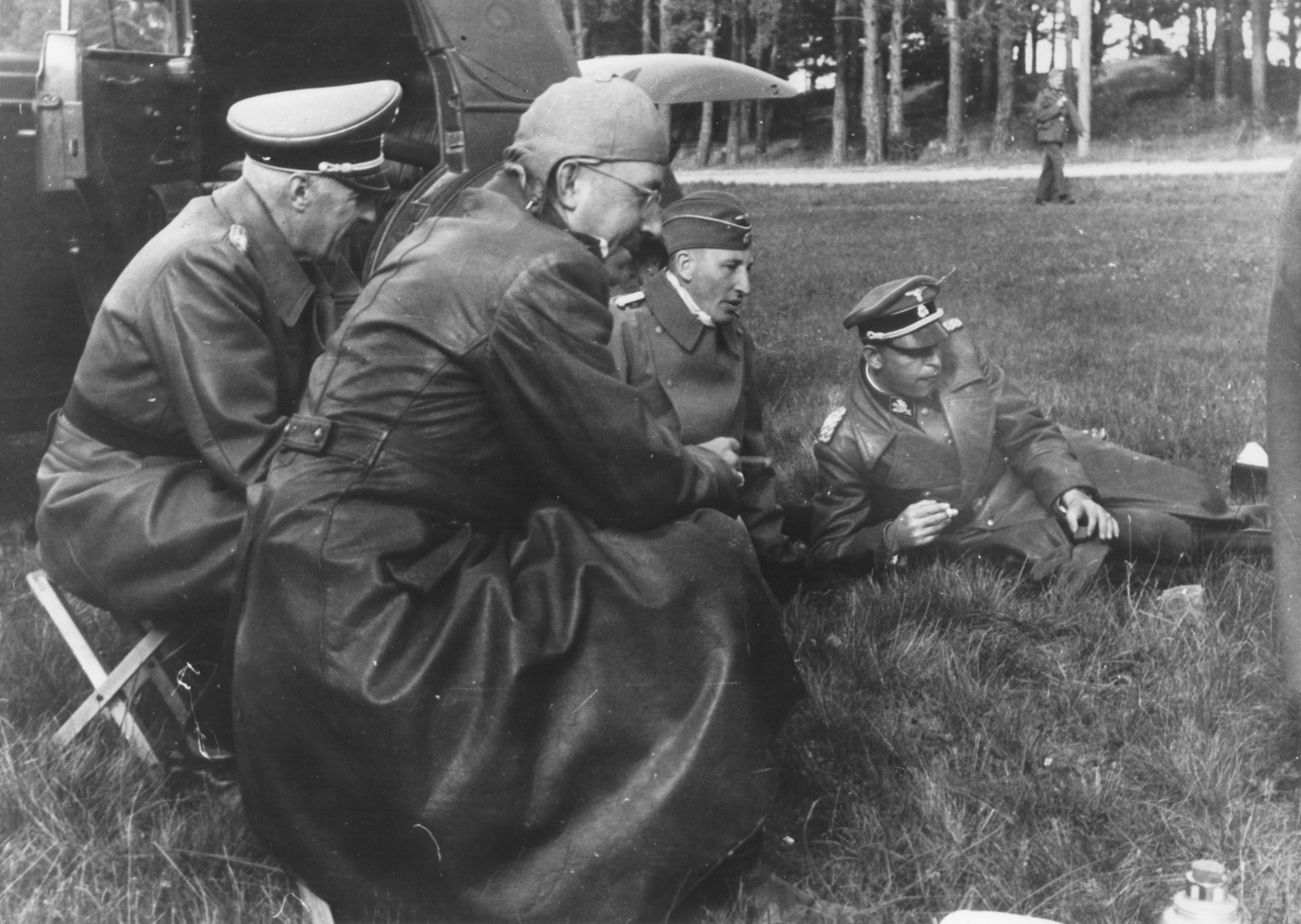 Reichsfuehrer-SS Heinrich Himmler smokes a cigar outside on the grass with Reinhard Heydrich and two other officers during a trip to Estonia.  Himmler is pictured in the foreground, and Heydrich, in the background in the center. SS Police Chief Leader Hans Adolf Pruetzmann is lying on the grass.