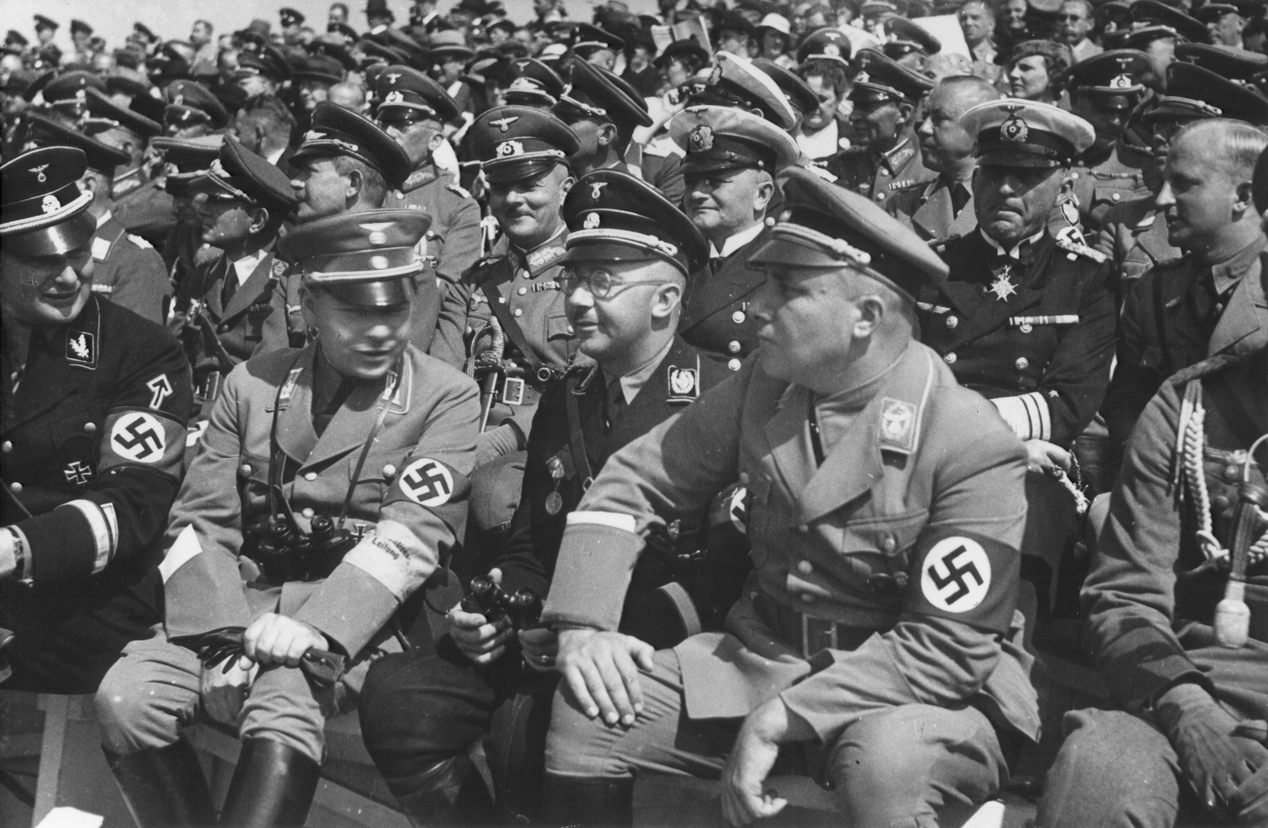 Heinrich Himmler sits in the audience during a Reichsparteitag (Reich Party Day) ceremony in Nuremberg.  Also pictured is Martin Bormann (front row, right) and Wilhem Keitel (second row, fourth from the left, behind and to the left of Himmler).