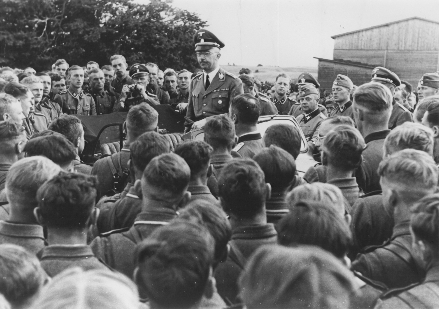 Reichsfuehrer-SS Heinrich Himmler addresses a group of soldiers in a cavalry regiment of the Waffen SS in the eastern territories.  Among those pictured are Kurt Knoblauch (standing near car) and Himmler's boyguard, Josef Kiermaier (holding a camera).