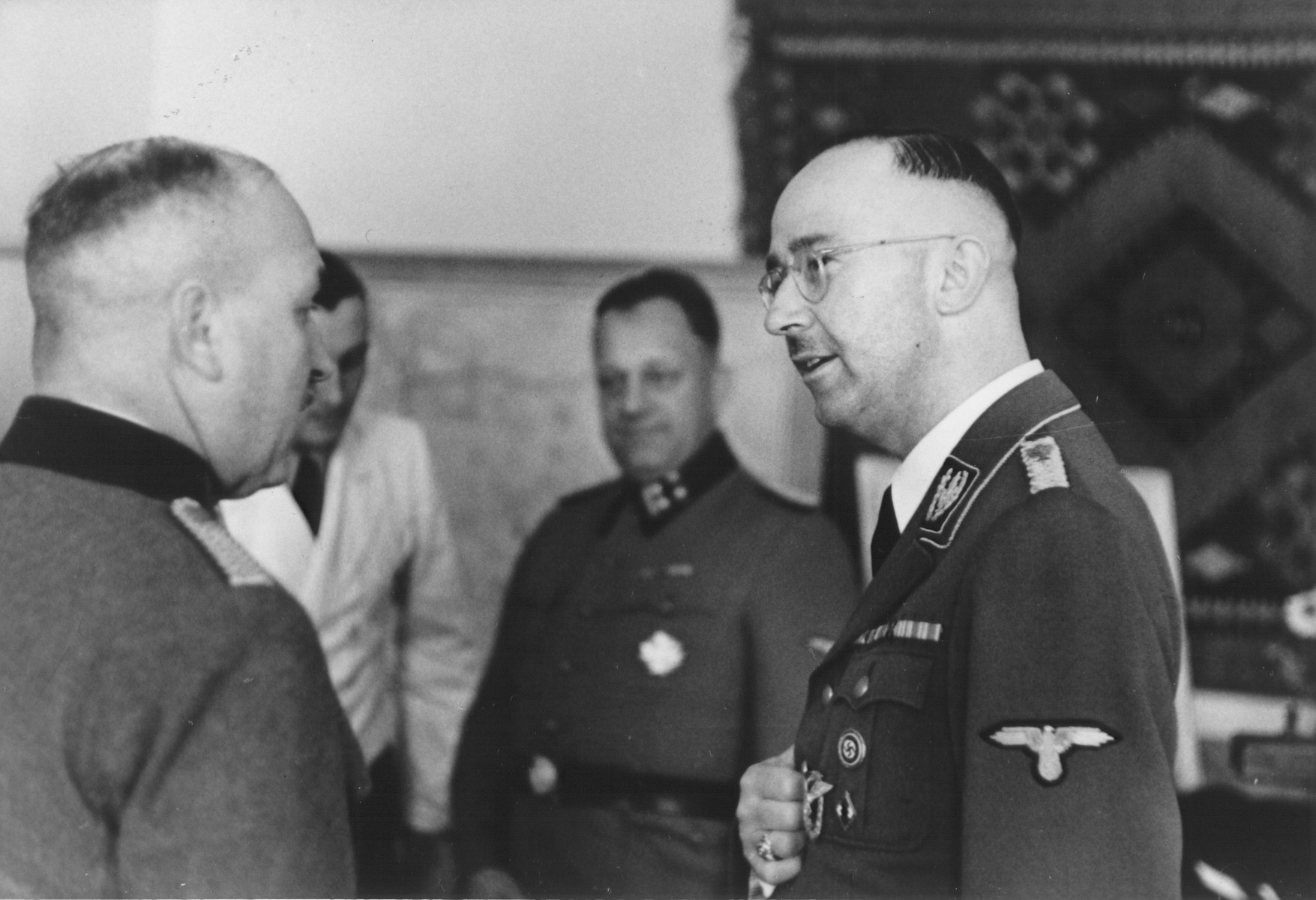 Reichsfuehrer-SS Heinrich Himmler accepts the well wishes of SS police officers on the occasion of his birthday at SS headquarters in the Hegewald bei Zhitomir compound.  The man speaking with Himmler is a member of the Ordnungspolizei.  Pictured in the center SS Obersturmbannfuehrer Josef Tiefenbacher.
