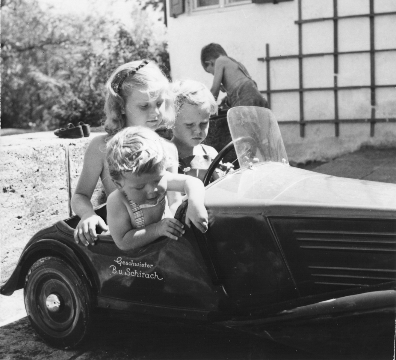 "Three young German children ride in a toy car.   Written on the side of the car is, ""Brothers and sisters Baldur von Schirach.""  Some of these children may be those of Baldur von Schirach.  He had three sons and a daughter."