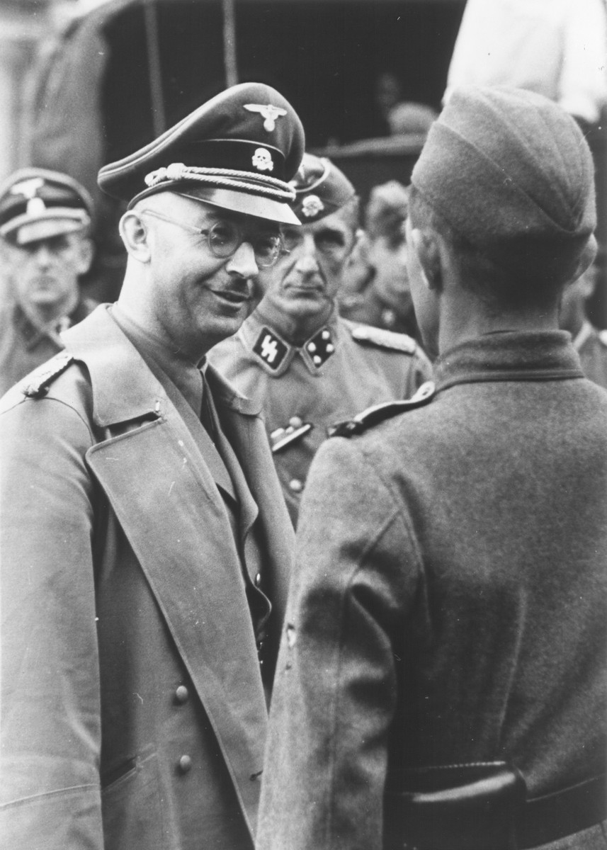 """Reichsfuehrer-SS Heinrich Himmler converses with an officer. On the back of this photograph are the following words: """"Mein Lieber Puppi vom Puzzi."""""""