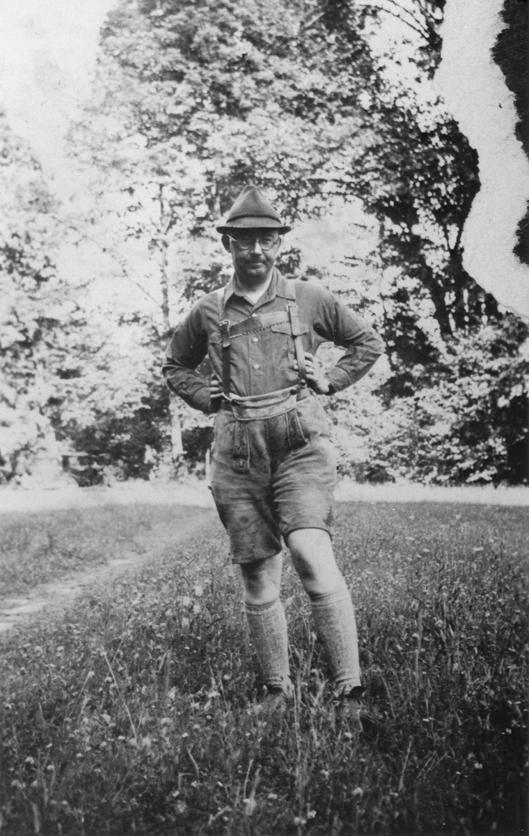 Portrait of Heinrich Himmler standing in a field wearing Lederhosen.