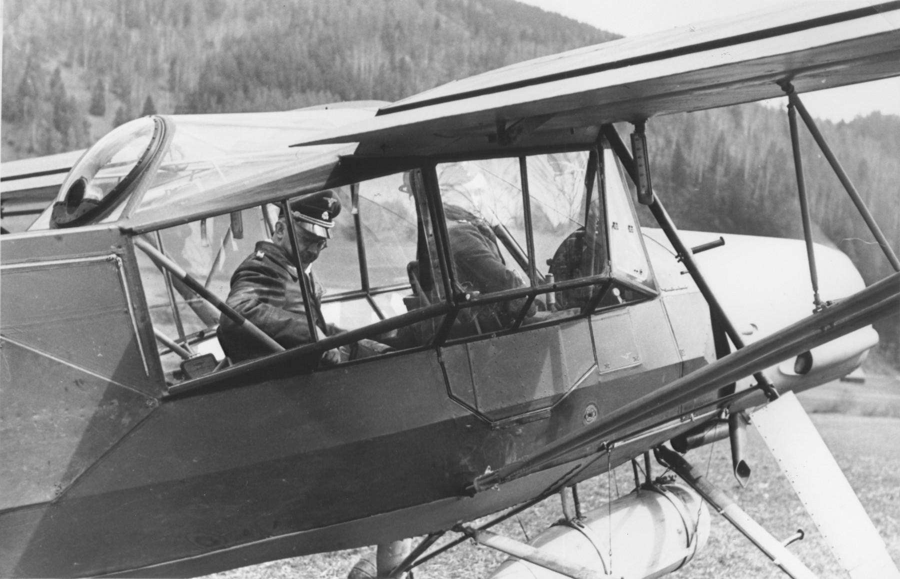 Reichsfuehrer-SS Heinrich Himmler riding as a passenger in an airplane.