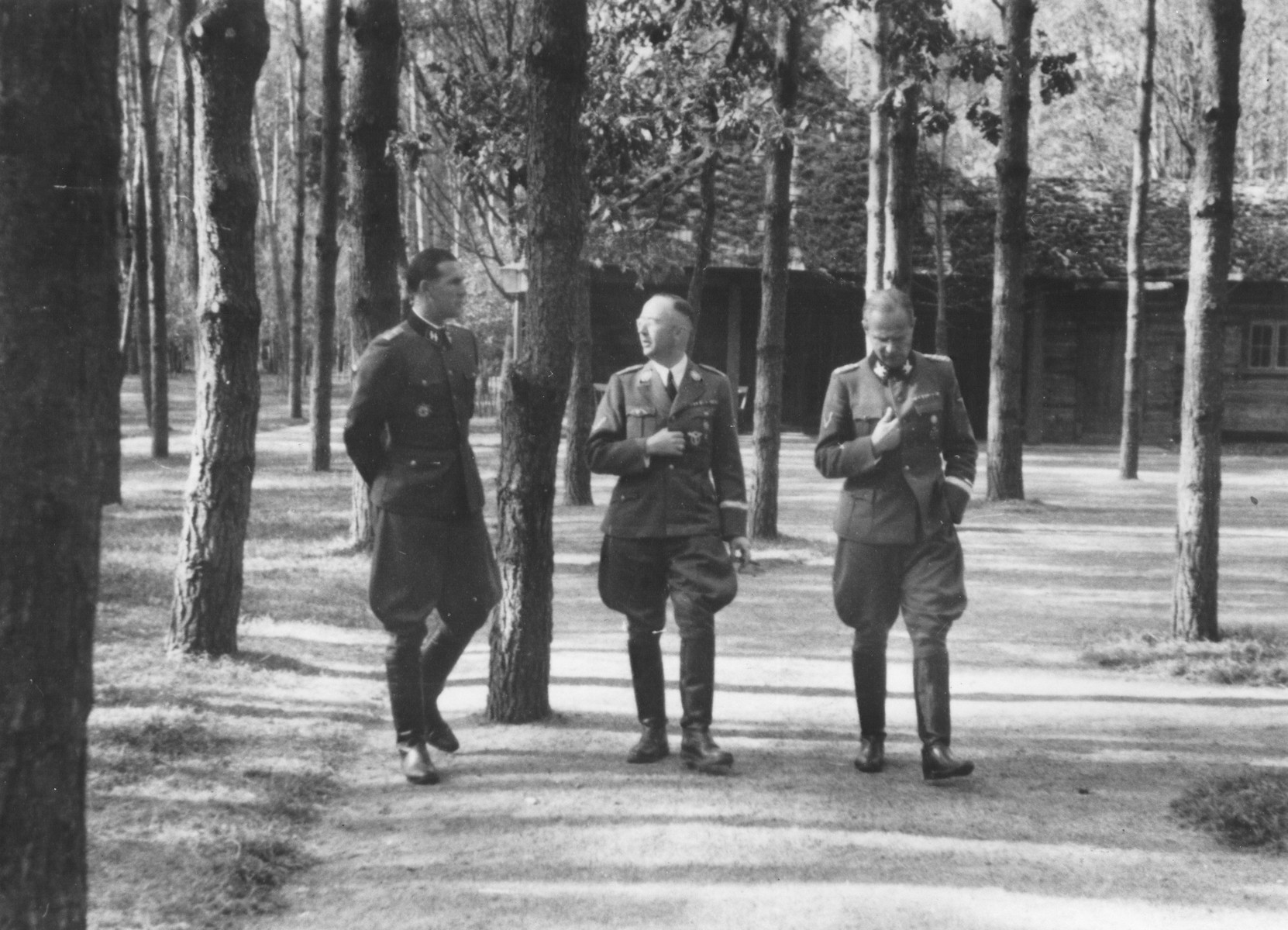 Reichsfuehrer-SS Heinrich Himmler converses outside in front of a cabin with two other Nazi leaders.  Pictured from left to right are: Richard Schulze-Kossens (Hitler's SS Adjutant), Himmler and Karl Wolff.