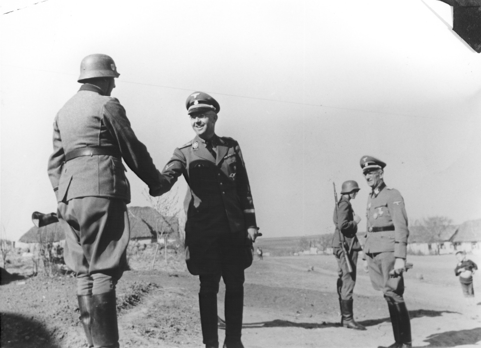 Reichsfuehrer-SS Heinrich Himmler shakes hands with a member of the Waffen-SS Armored Division Wiking during an official visit.  SS-Obergruppenfuehrer and General Herbert O. Gille (commander of the Wiking Division from May 1943 until August 1944) is pictured at the right wearing glasses.