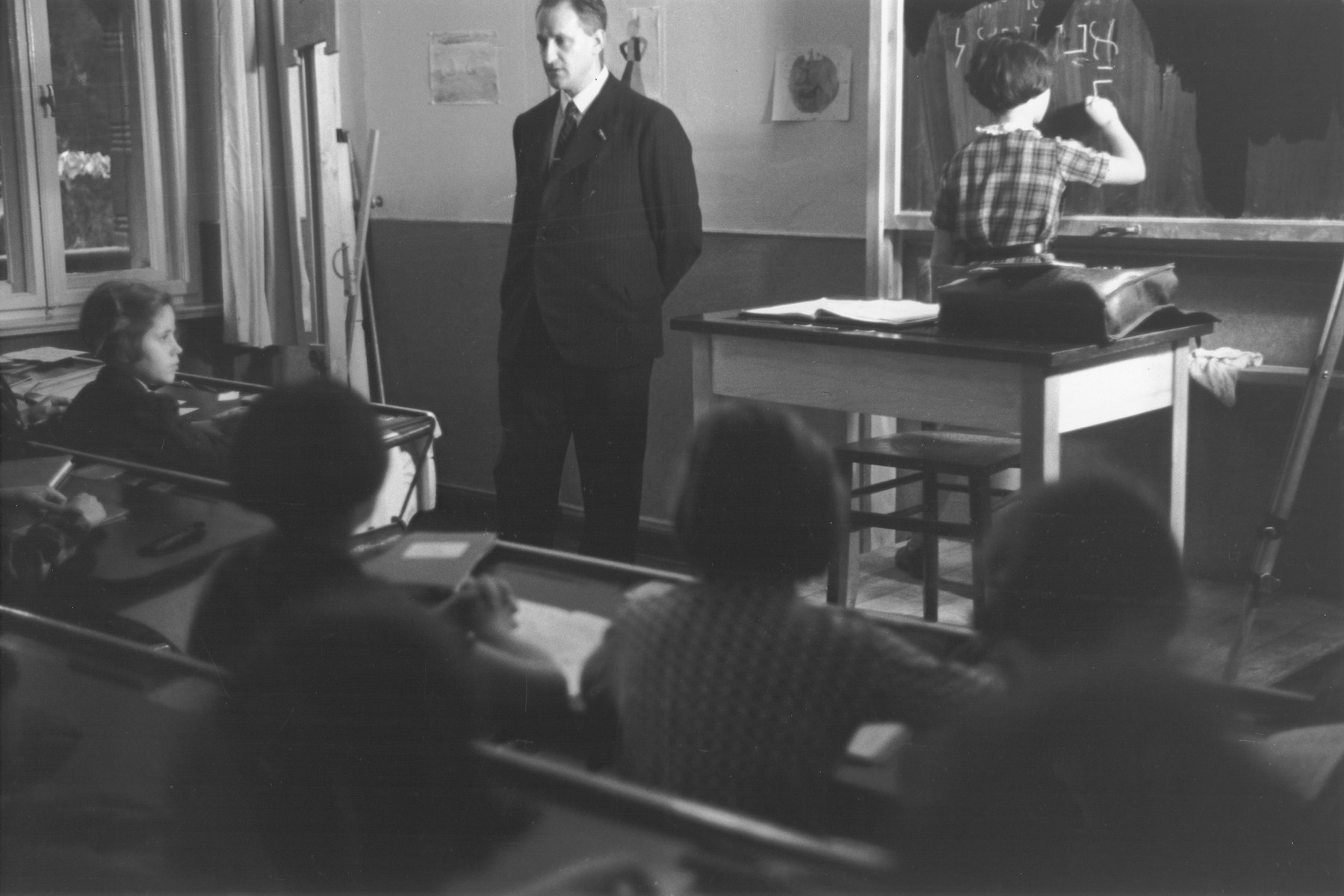 A Hebrew teacher at the Goldschmidt Jewish private school in Berlin-Grunewald instructs a class while one of his pupils conjugates a verb at the chalkboard.
