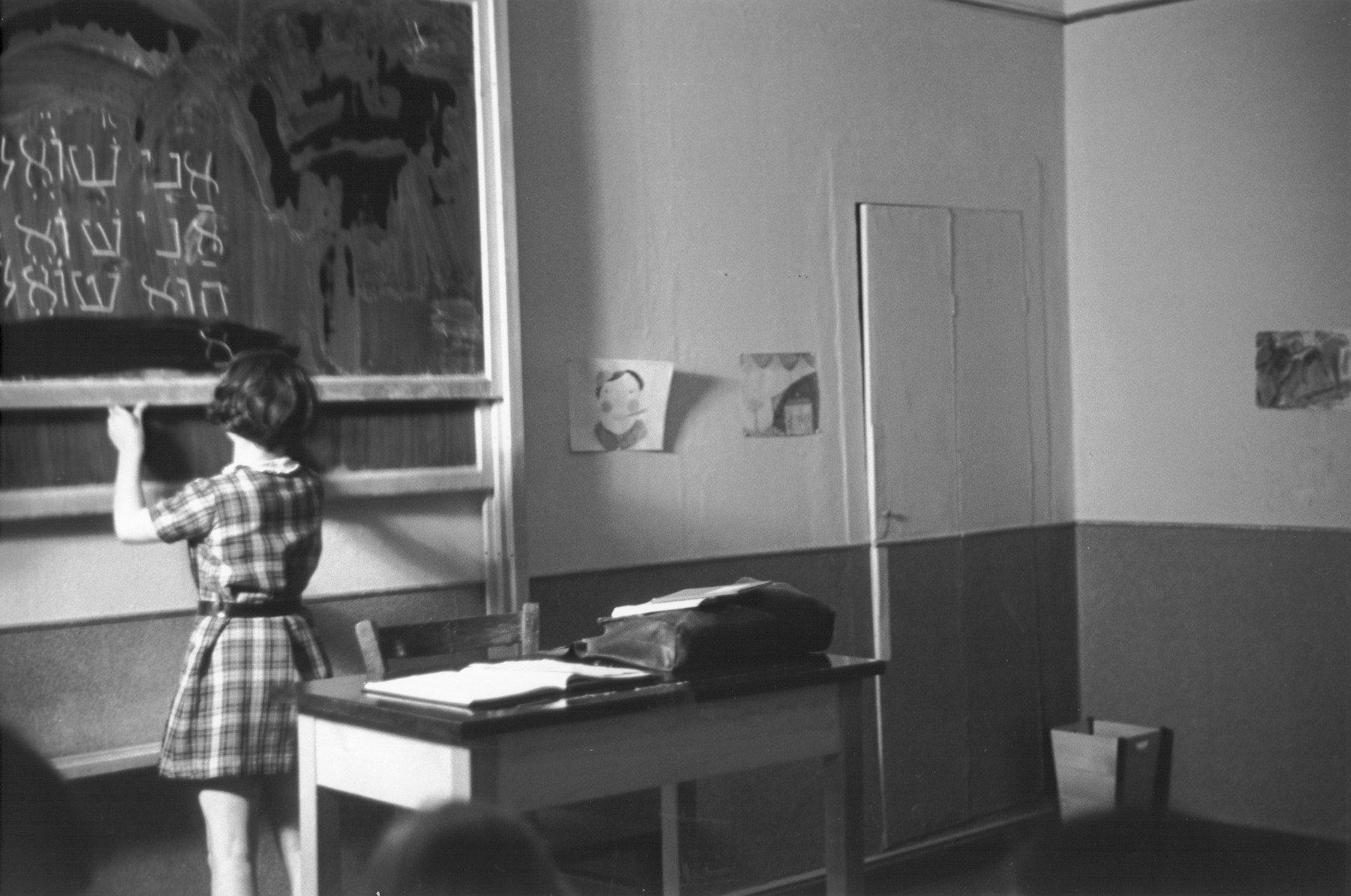 "A pupil at the Goldschmidt Jewish private school in Berlin-Grunewald writes the conjugation of the Hebrew verb ""to ask"" on the chalkboard."