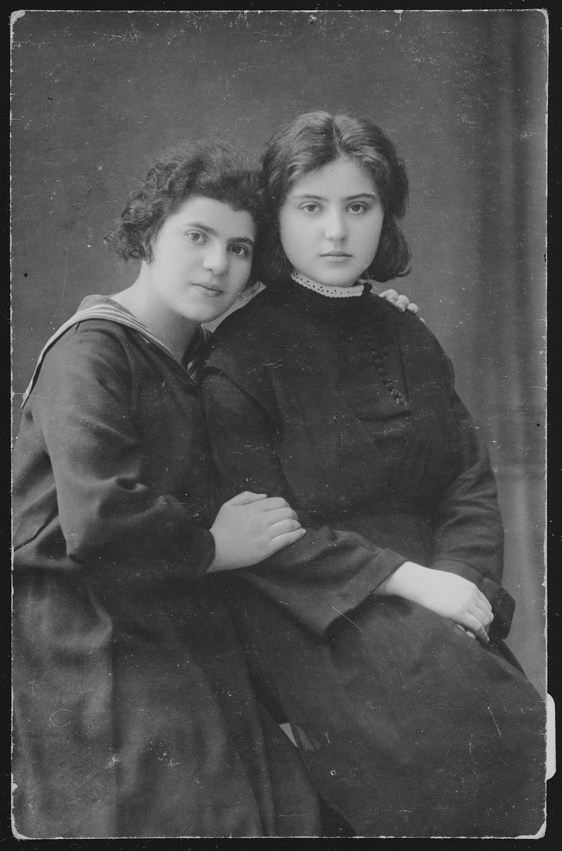 """Studio portrait of two teenage girls who were students of Dr. Shaul Kaleko-Barkali.  Pesia is on the right with a friend.  The photo is inscribed in Hebrew: """"Remember me wherever you will be."""" The girls' fate is unknown."""
