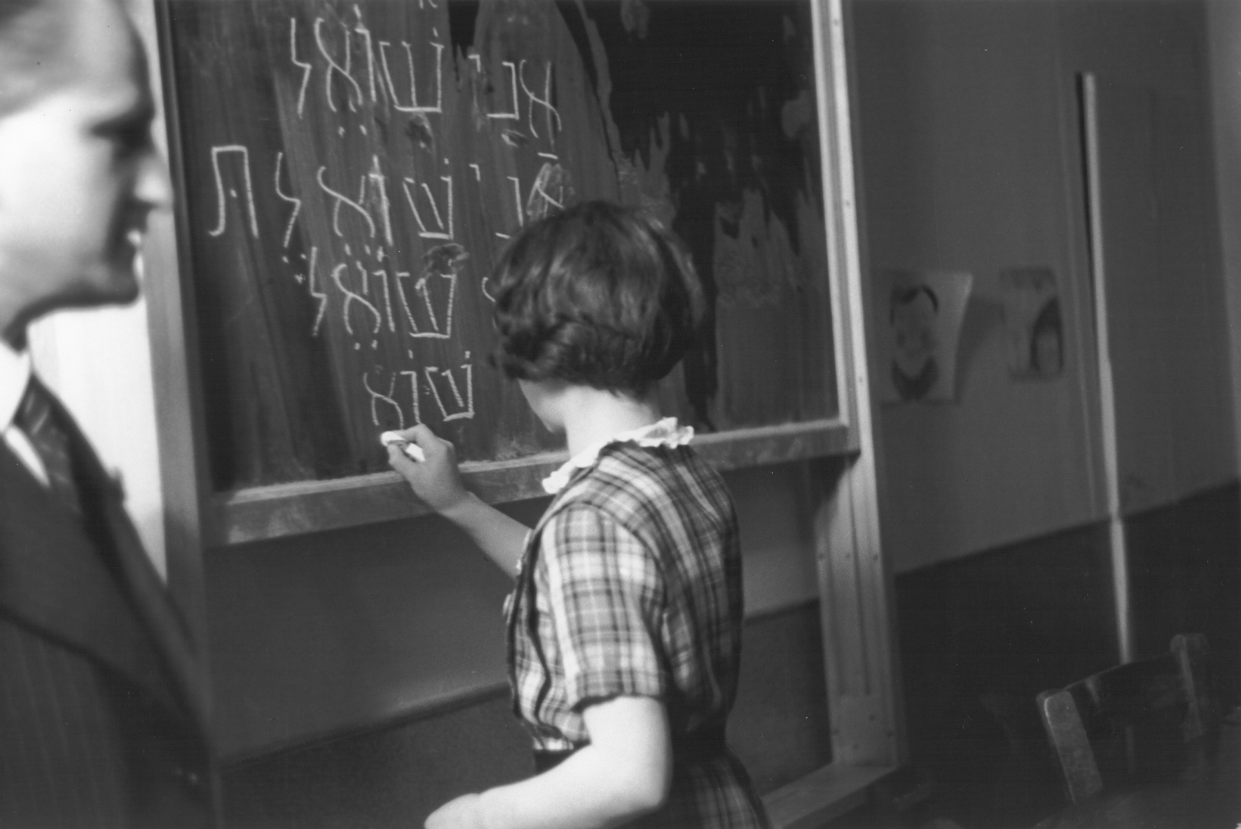 """A pupil at the Goldschmidt Jewish private school in Berlin-Grunewald writes the conjugation of the Hebrew verb """"to ask"""" on the chalkboard."""