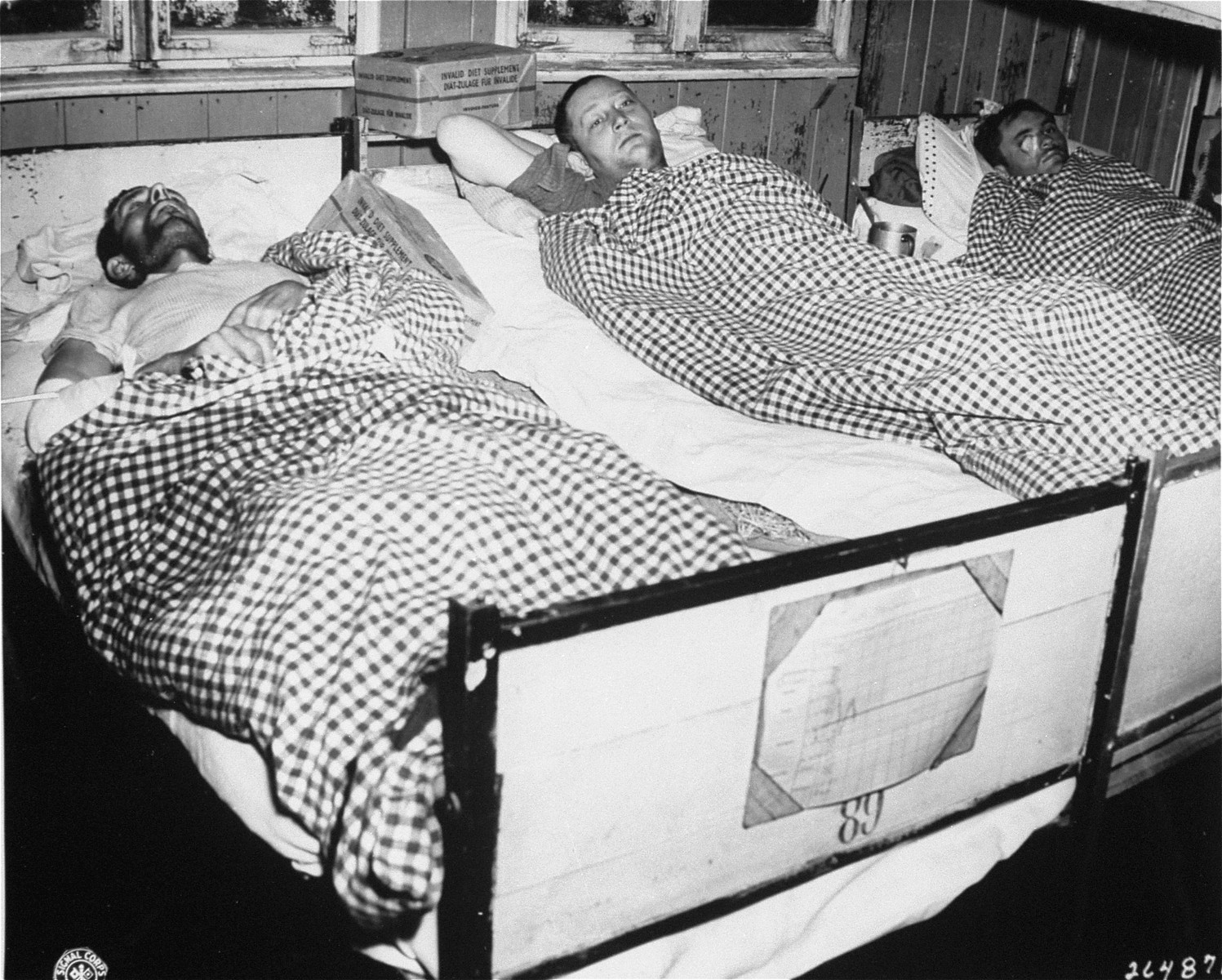 Three survivors infected with typhus lie in beds in the hospital barracks in the Flossenbuerg concentration camp.