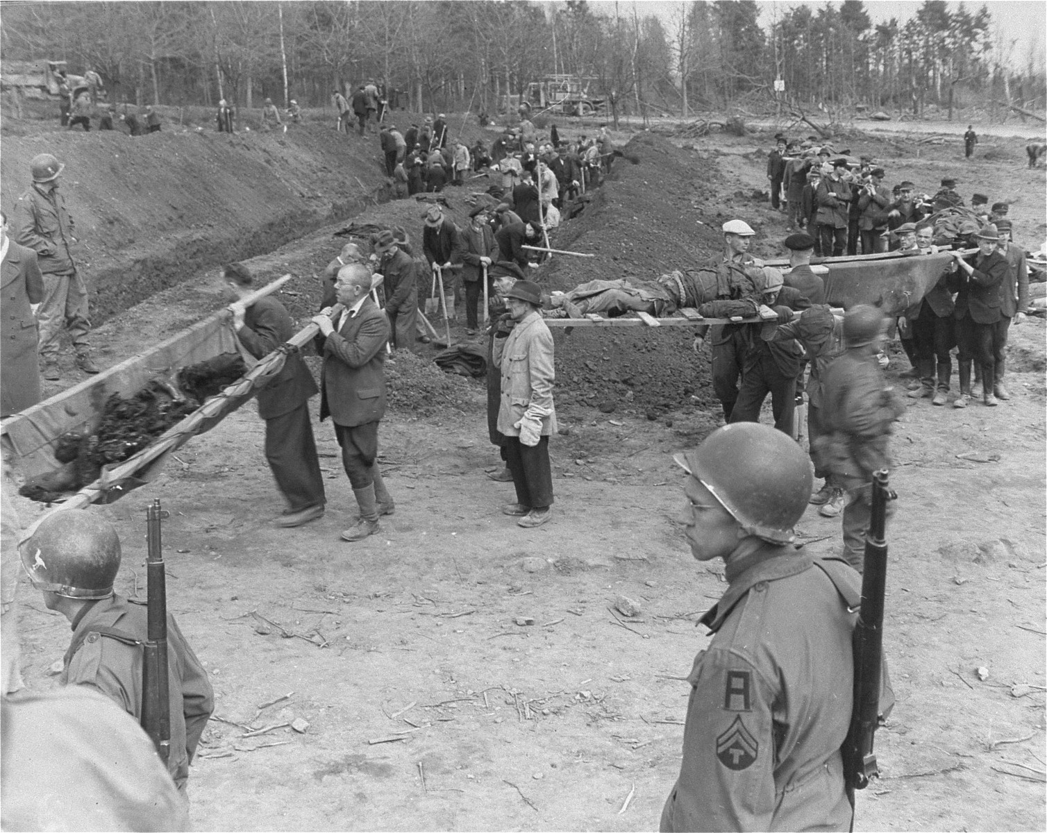 American troops look on as German civilians carry corpses from the grounds of the Nordhausen concentration camp to mass graves for burial.